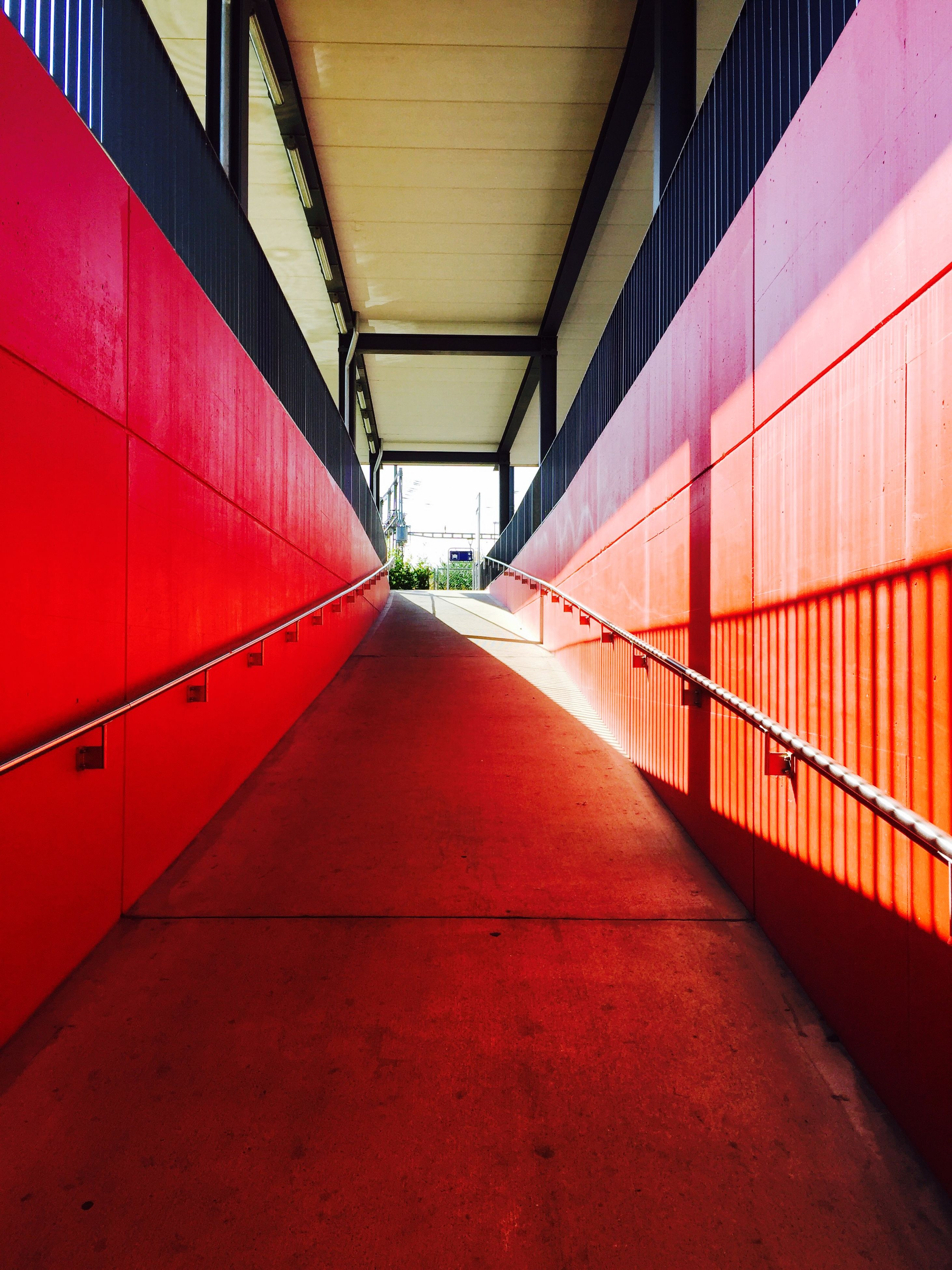 architecture, the way forward, built structure, red, diminishing perspective, empty, indoors, vanishing point, narrow, long, building exterior, wall - building feature, walkway, surface level, railing, corridor, no people, in a row, absence, building