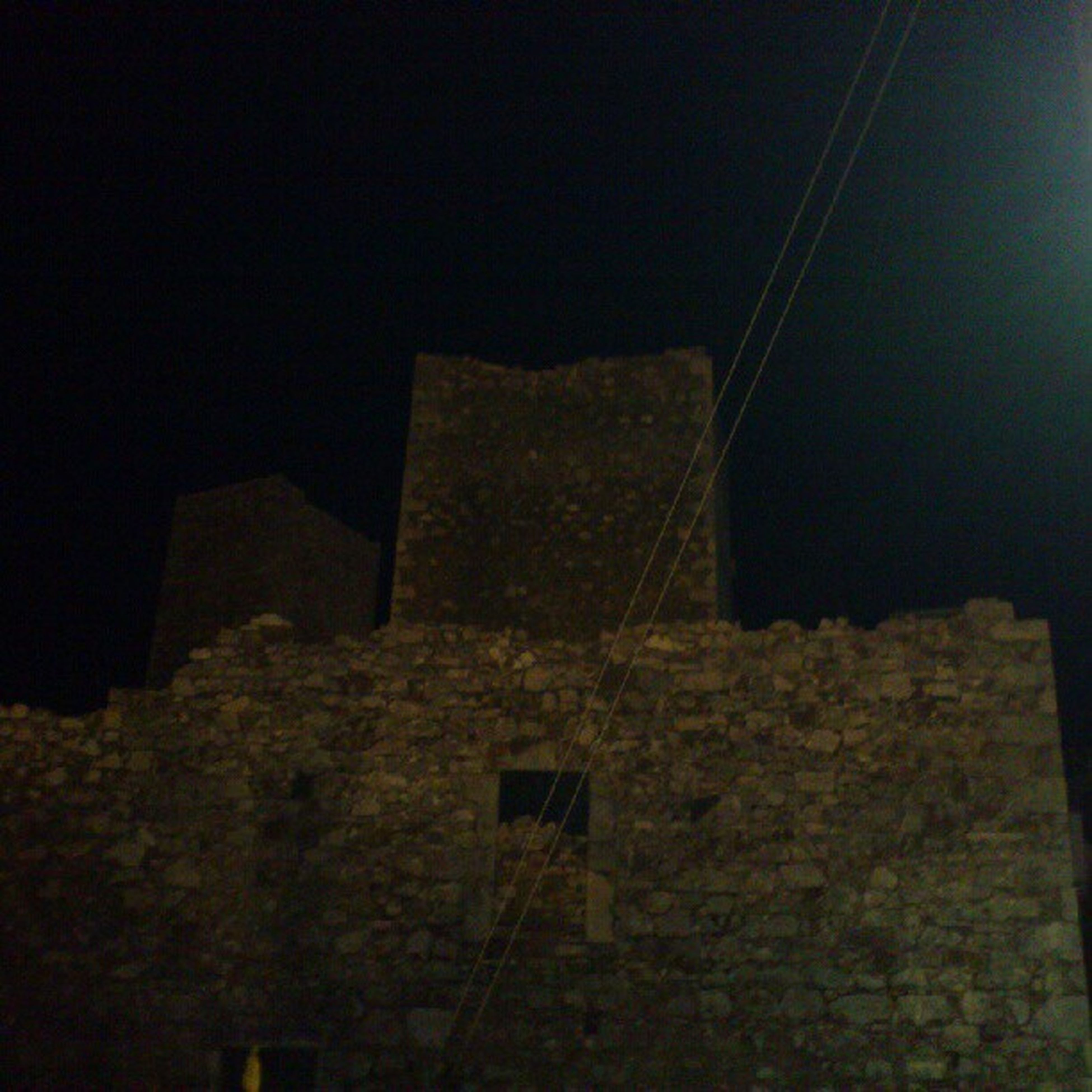 architecture, built structure, low angle view, night, building exterior, wall - building feature, stone wall, copy space, illuminated, old, brick wall, dark, no people, indoors, abandoned, clear sky, wall, building, damaged