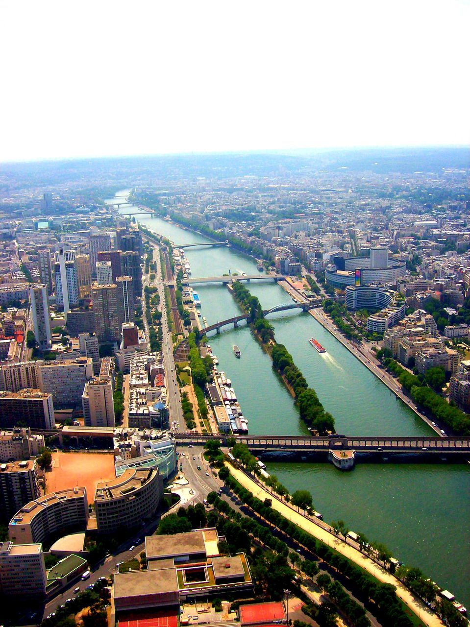 architecture, cityscape, city, building exterior, built structure, travel destinations, aerial view, high angle view, river, skyscraper, crowded, outdoors, day, bridge - man made structure, clear sky, sky, modern, water, urban skyline