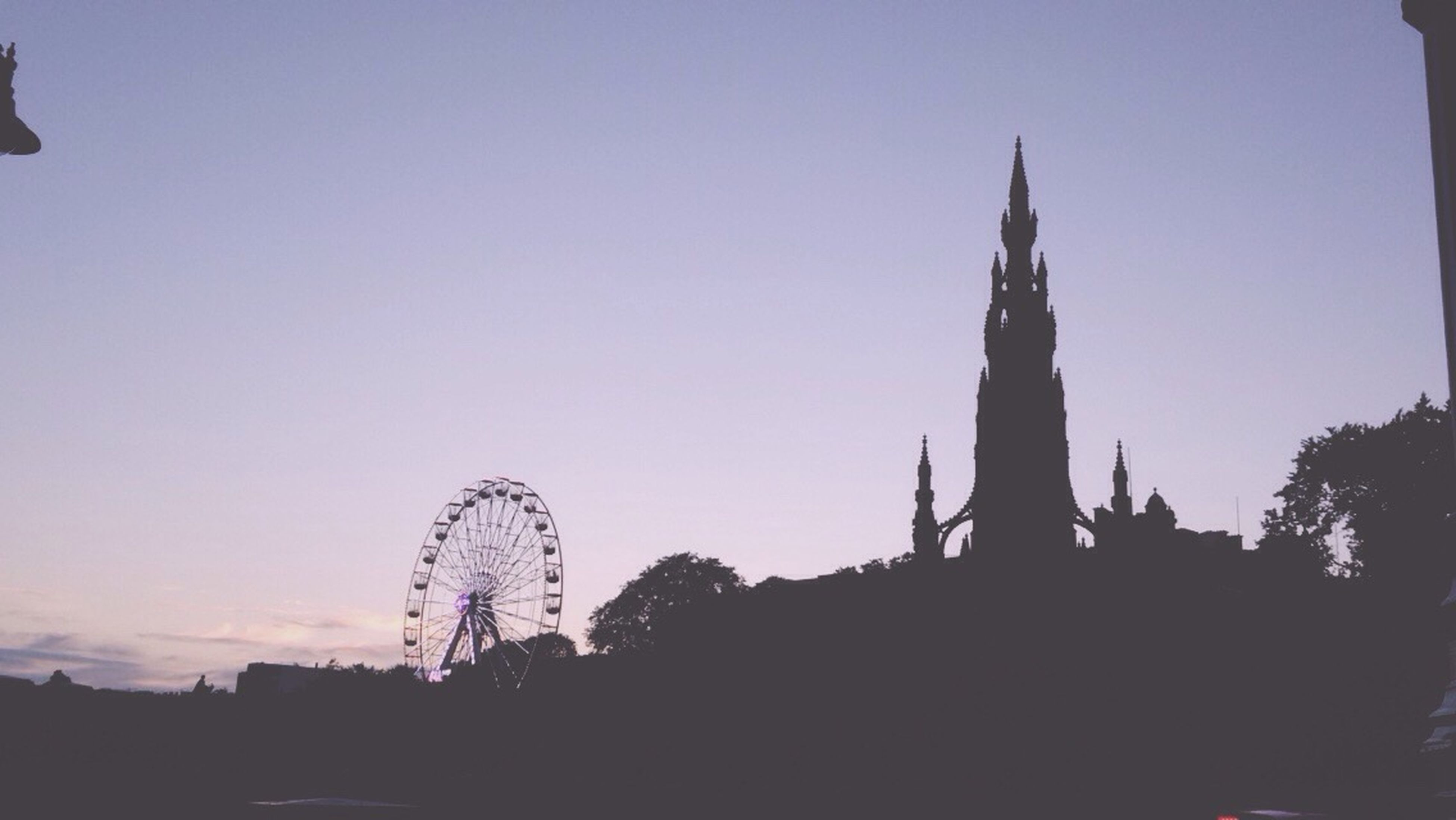 silhouette, clear sky, low angle view, outline, outdoors, high section, sky, amusement park, no people
