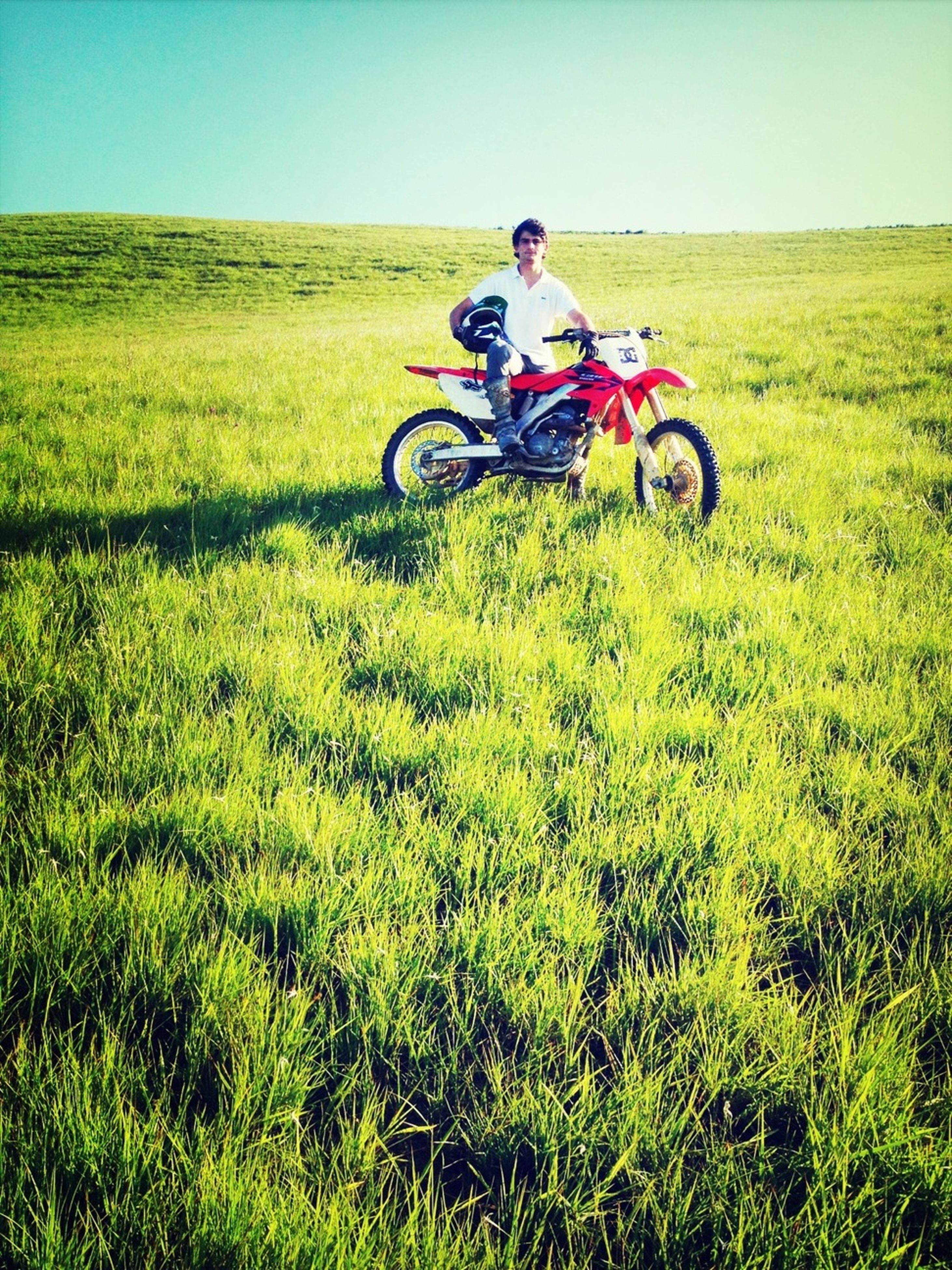 transportation, land vehicle, mode of transport, bicycle, grass, field, riding, leisure activity, lifestyles, grassy, landscape, clear sky, men, green color, sunlight, cycling, growth, full length