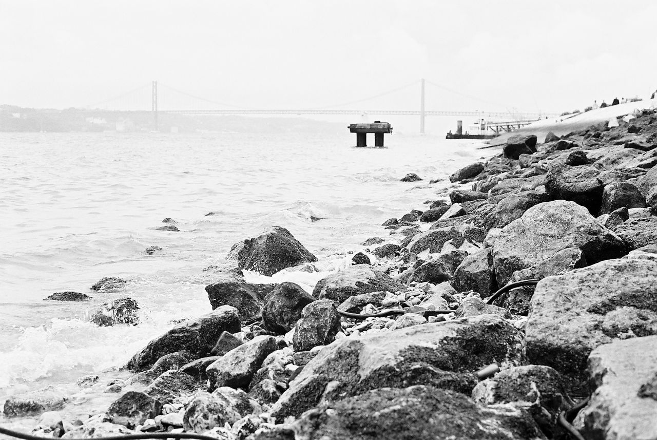 sea, rock - object, water, connection, nature, outdoors, day, bridge - man made structure, sky, scenics, beauty in nature, architecture, no people, suspension bridge, beach, horizon over water, mountain