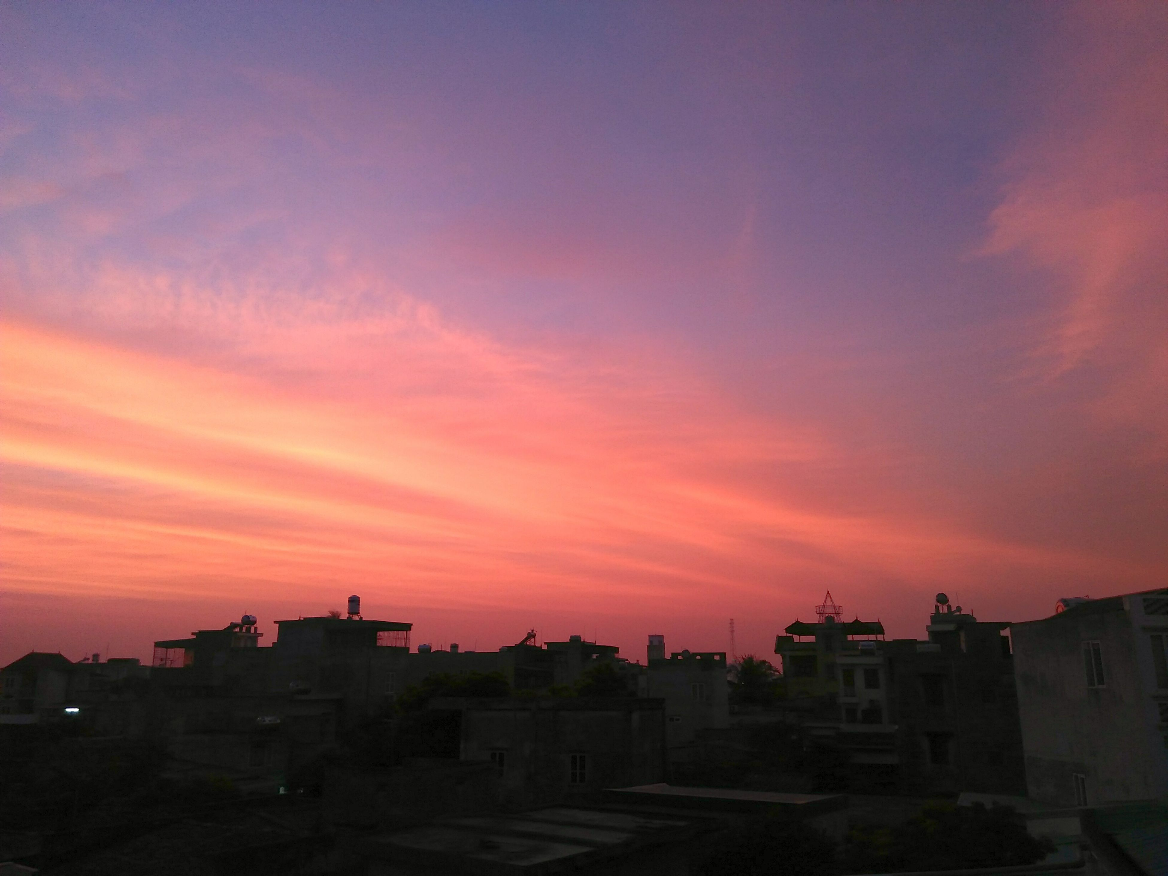architecture, sunset, built structure, building exterior, orange color, sky, city, cloud - sky, cloud, scenics, city life, beauty in nature, romantic sky, exterior, outdoors, dramatic sky, majestic, nature, residential district, tranquility, no people, tranquil scene, atmospheric mood, pink color, town