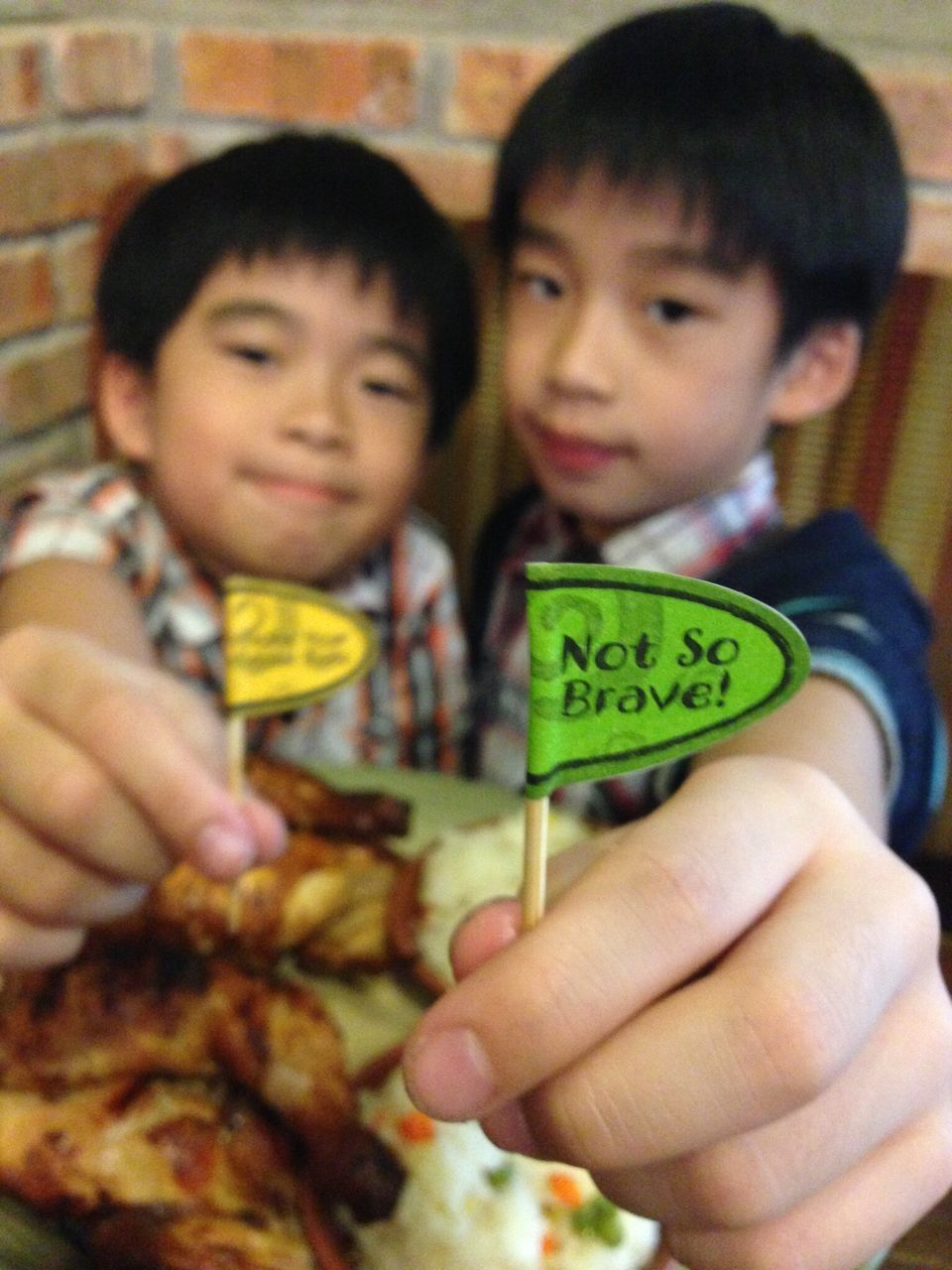 Portrait Of Boys Showing Message On Stick While Having Food At Table In Restaurant