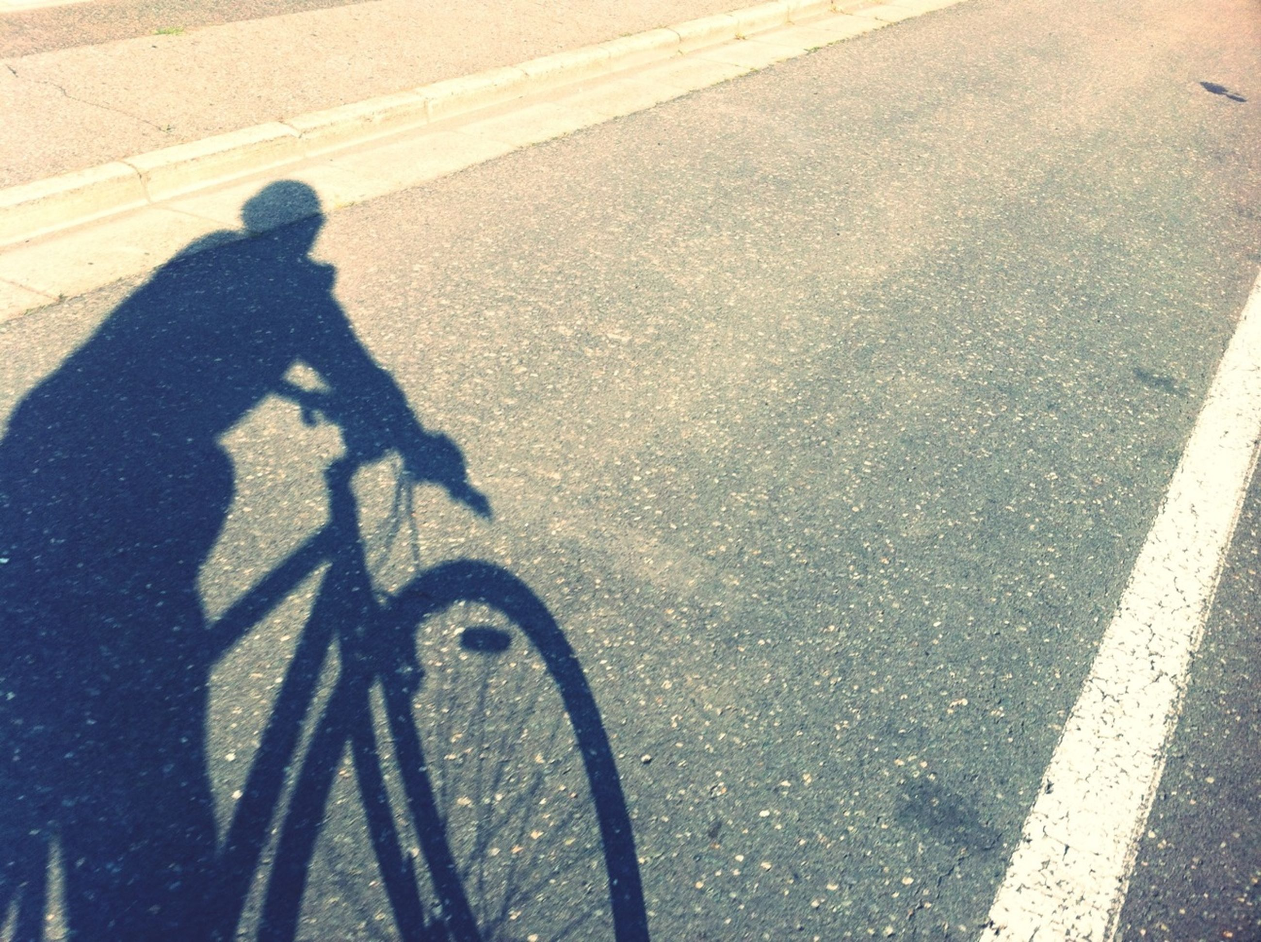 transportation, street, road marking, road, shadow, high angle view, bicycle, asphalt, lifestyles, sunlight, leisure activity, men, focus on shadow, land vehicle, cycling, mode of transport, unrecognizable person, outdoors