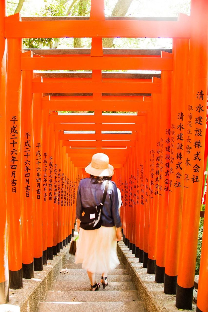 Rear View Of Woman Walking Through Torii Gates At Hie Shrine