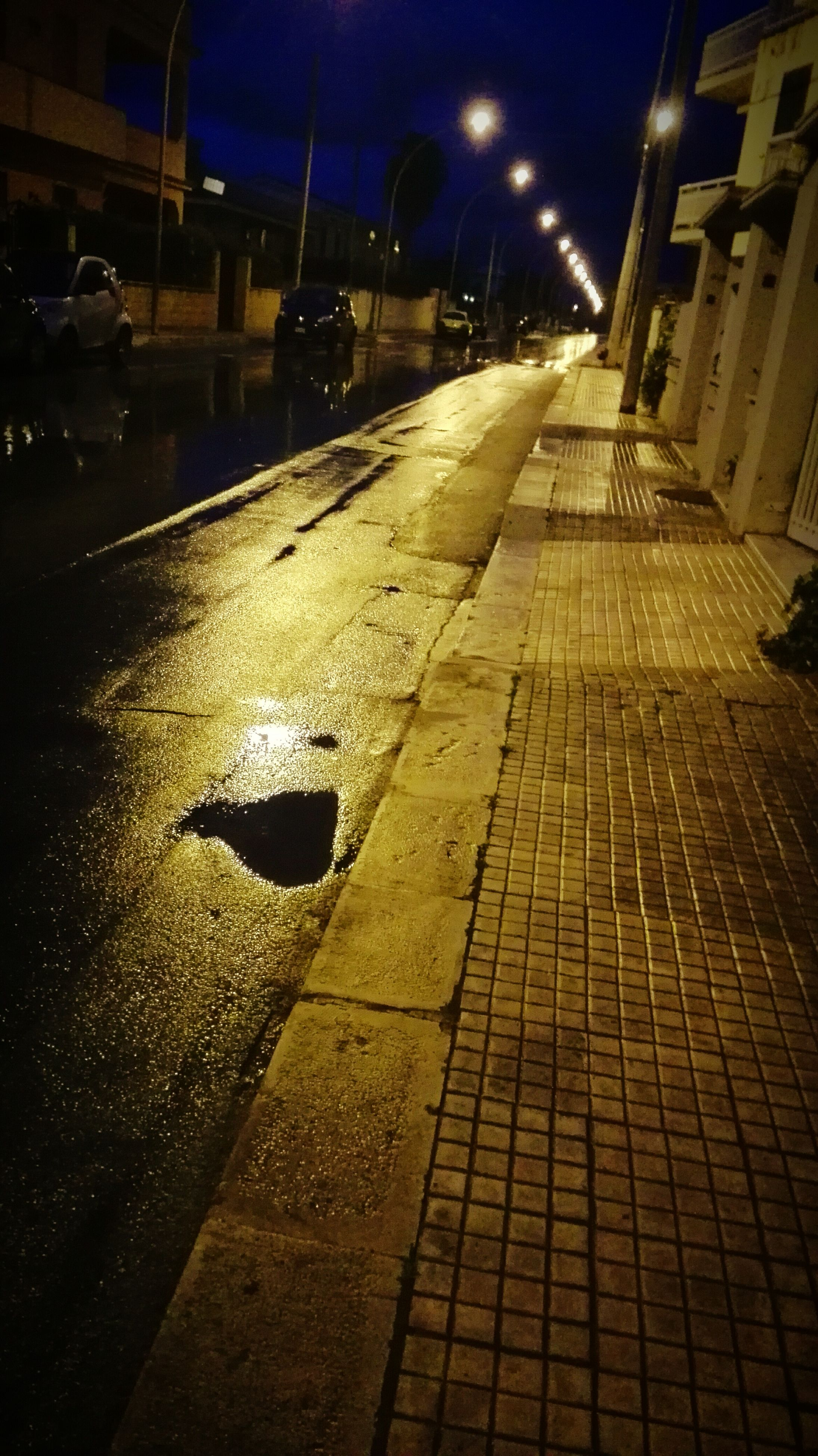 night, architecture, illuminated, building exterior, built structure, street, city, the way forward, road, street light, building, outdoors, shadow, lighting equipment, cobblestone, puddle, no people, city street, road marking, light - natural phenomenon