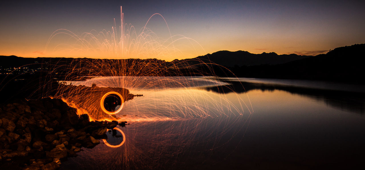 Person Light Painting By Lake At Sunset