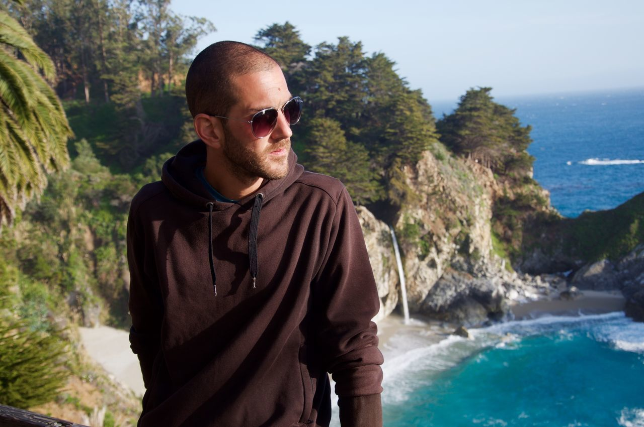 Fashionable Man Standing Against Mcway Falls At Beach