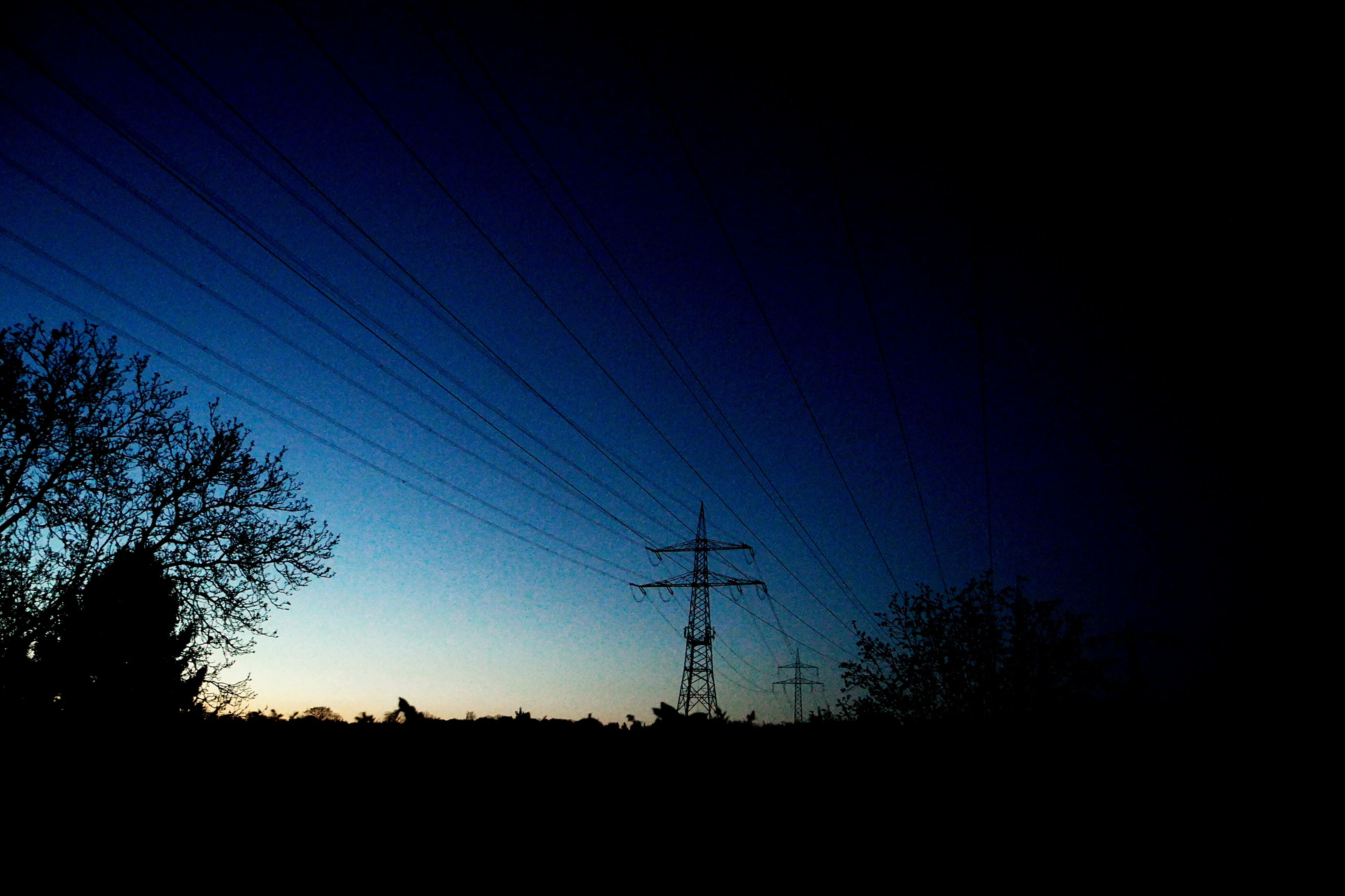 silhouette, power line, electricity pylon, electricity, power supply, low angle view, tranquility, tranquil scene, fuel and power generation, scenics, sunset, sky, beauty in nature, nature, tree, technology, dusk, landscape, clear sky, dark