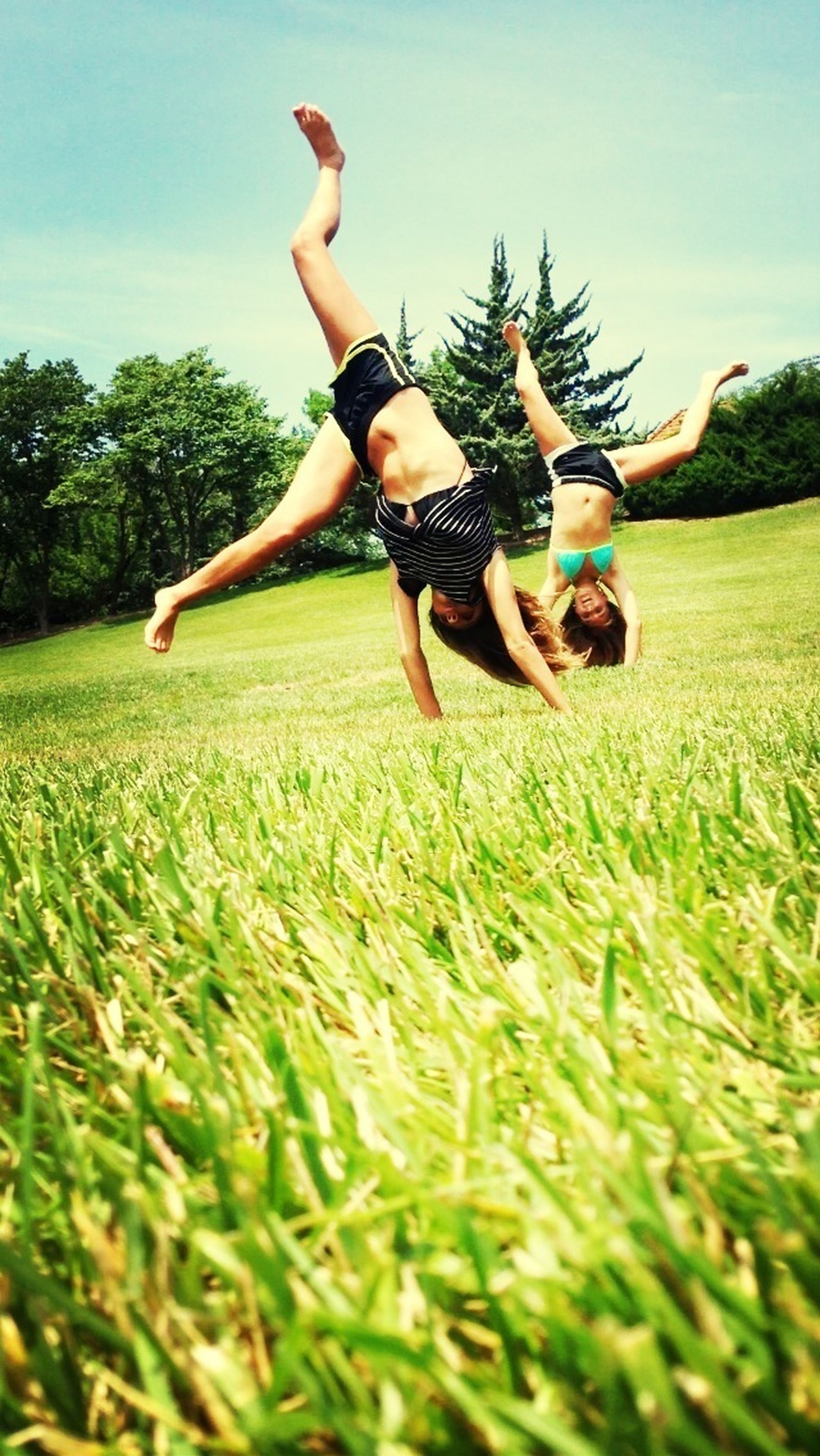 grass, leisure activity, lifestyles, field, childhood, full length, fun, grassy, enjoyment, mid-air, playful, green color, playing, togetherness, boys, casual clothing, sky