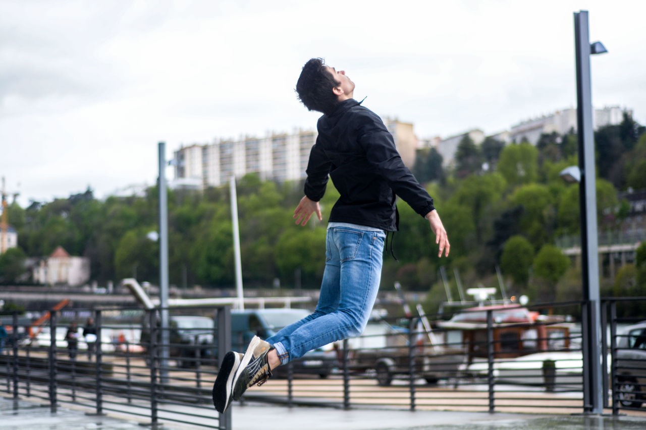 one person, real people, focus on foreground, full length, outdoors, casual clothing, leisure activity, day, jumping, mid-air, motion, lifestyles, sky, building exterior, young adult, architecture, young women, energetic, tree, city, people