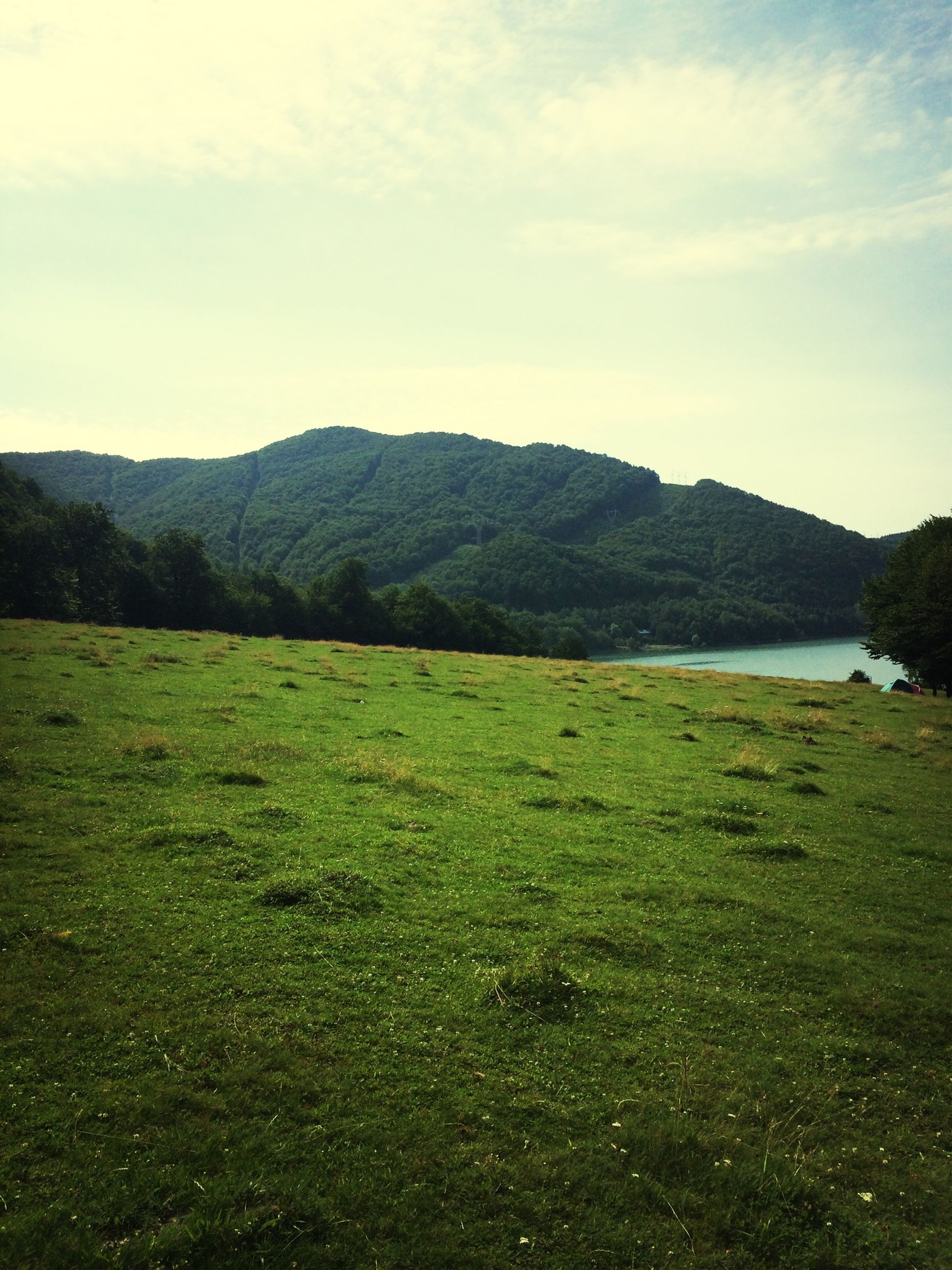 grass, mountain, tranquil scene, sky, tranquility, scenics, landscape, beauty in nature, water, nature, green color, grassy, mountain range, field, lake, cloud - sky, idyllic, cloud, non-urban scene, outdoors
