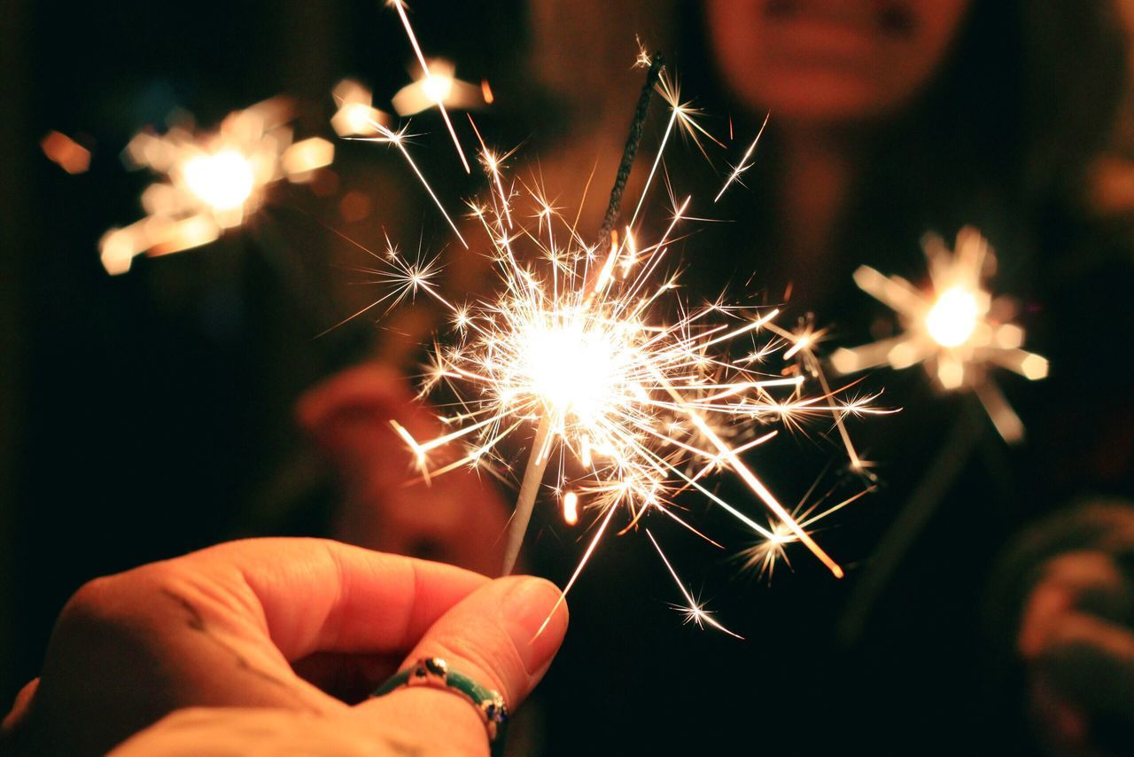 Human Hand Holding Human Body Part Lifestyles Real People Unrecognizable Person One Person Human Finger Sparkler Leisure Activity Close-up Burning Personal Perspective Celebration Blurred Motion Fingernail Sparks Motion Outdoors Night Christmas Lights Christmastime Emotions