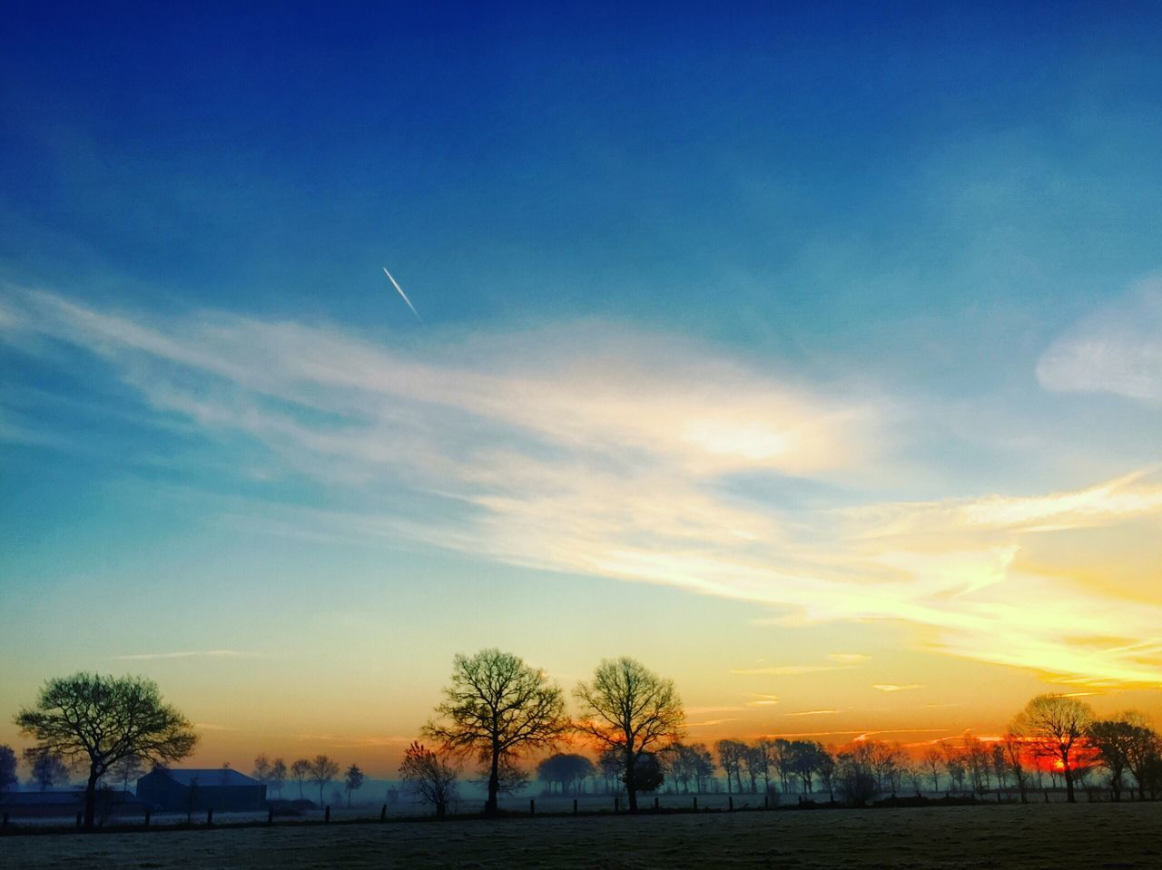 Countryside landscape at sunrise Beauty In Nature Cold Temperature Scenics Nature Winter Sky Tranquil Scene Sunset Tranquility Tree Snow Cloud - Sky Silhouette Landscape Outdoors Blue No People Bare Tree Water Vapor Trail