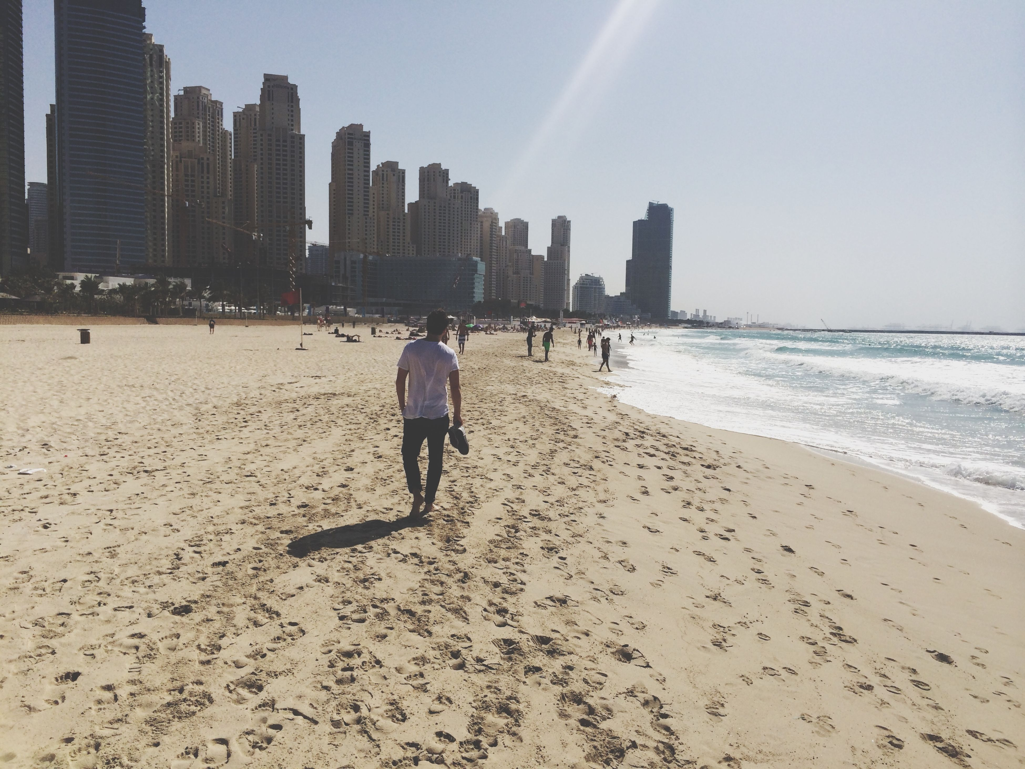 beach, sand, sea, lifestyles, shore, leisure activity, built structure, architecture, building exterior, walking, water, men, person, sunlight, vacations, full length, tourist, large group of people, sky