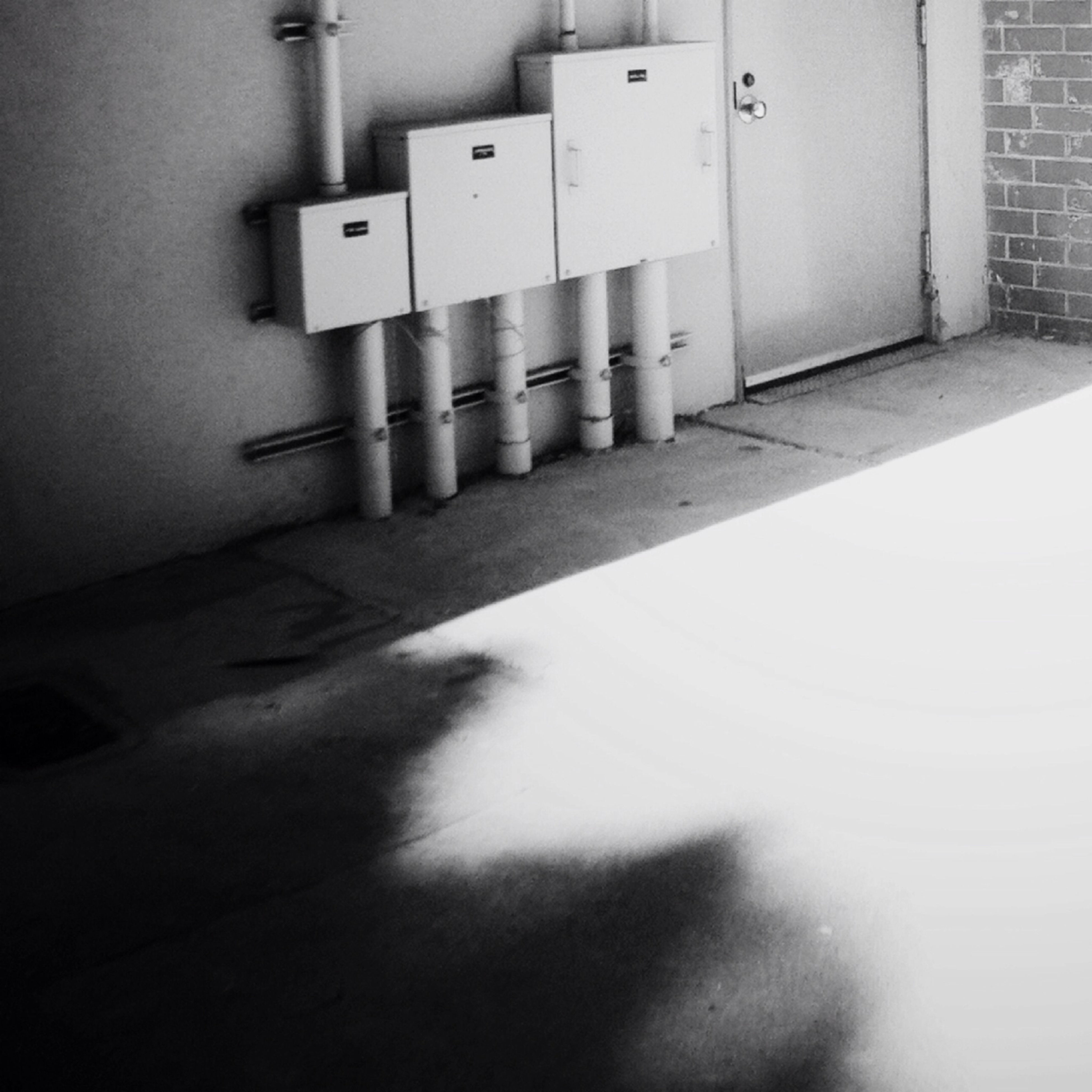 indoors, architecture, built structure, wall - building feature, no people, in a row, wall, shadow, close-up, illuminated, building, door, building exterior, the way forward, white color, high angle view, diminishing perspective, empty, day, pattern