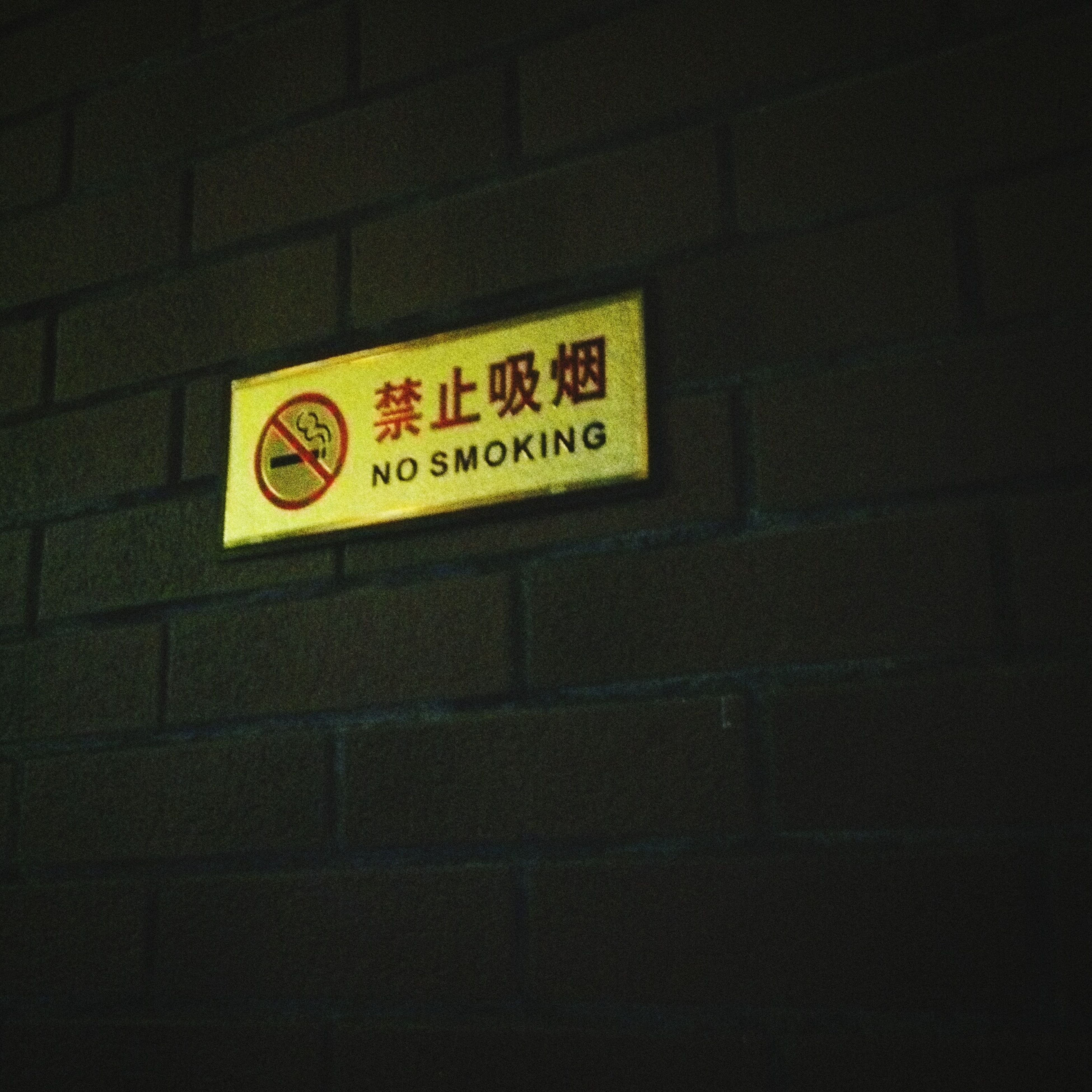 text, western script, communication, information sign, sign, capital letter, wall - building feature, information, guidance, non-western script, built structure, architecture, illuminated, wall, arrow symbol, night, yellow, directional sign, warning sign, no people