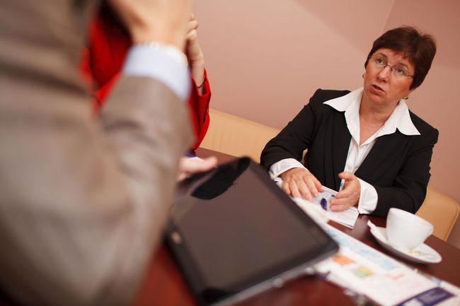 Businesswoman Caucasian Desk Engaged Explaining  Explanation Human Hand Mature Meeting Office People Professional Real People Sat Table Teamwork