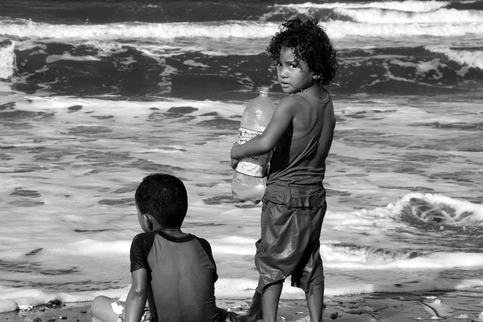 Collecting recycling from a filthy beach Blackandwhite Childhood Children Clutching Rubbish Filthy Beach Honduras Kids On A Beach Looking At Camera Rubbish