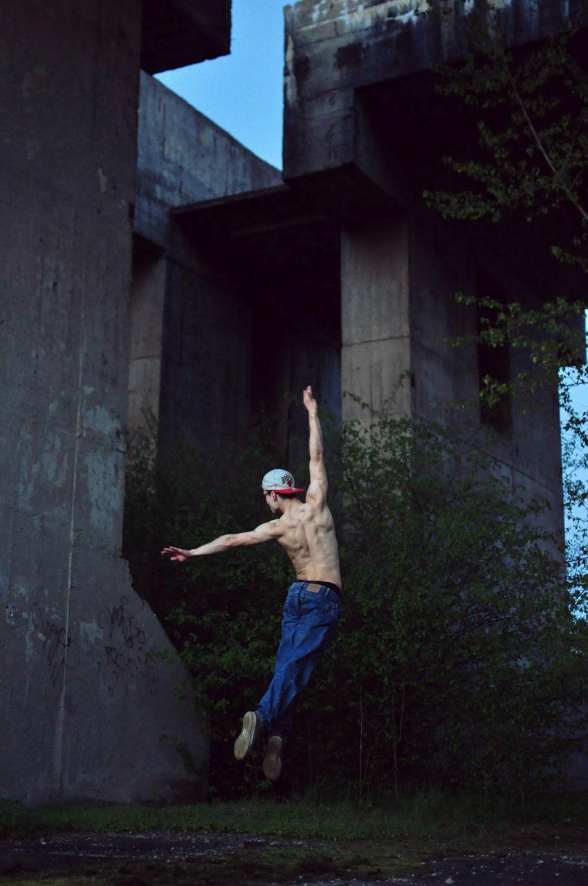 Rear View Of Shirtless Dancer Dancing On Field Against Bridge