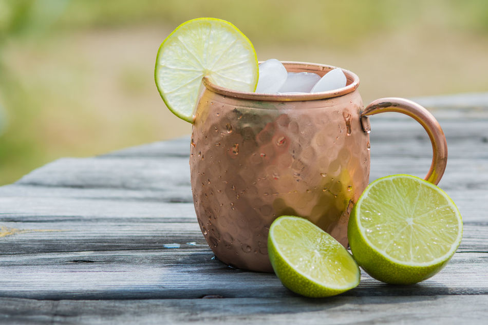 Moscow mule in a copper mug garnished with limes Adult Beverage Alcoholic Drink Beverage Copper Mug Drink Ice Lime Moscow Mule