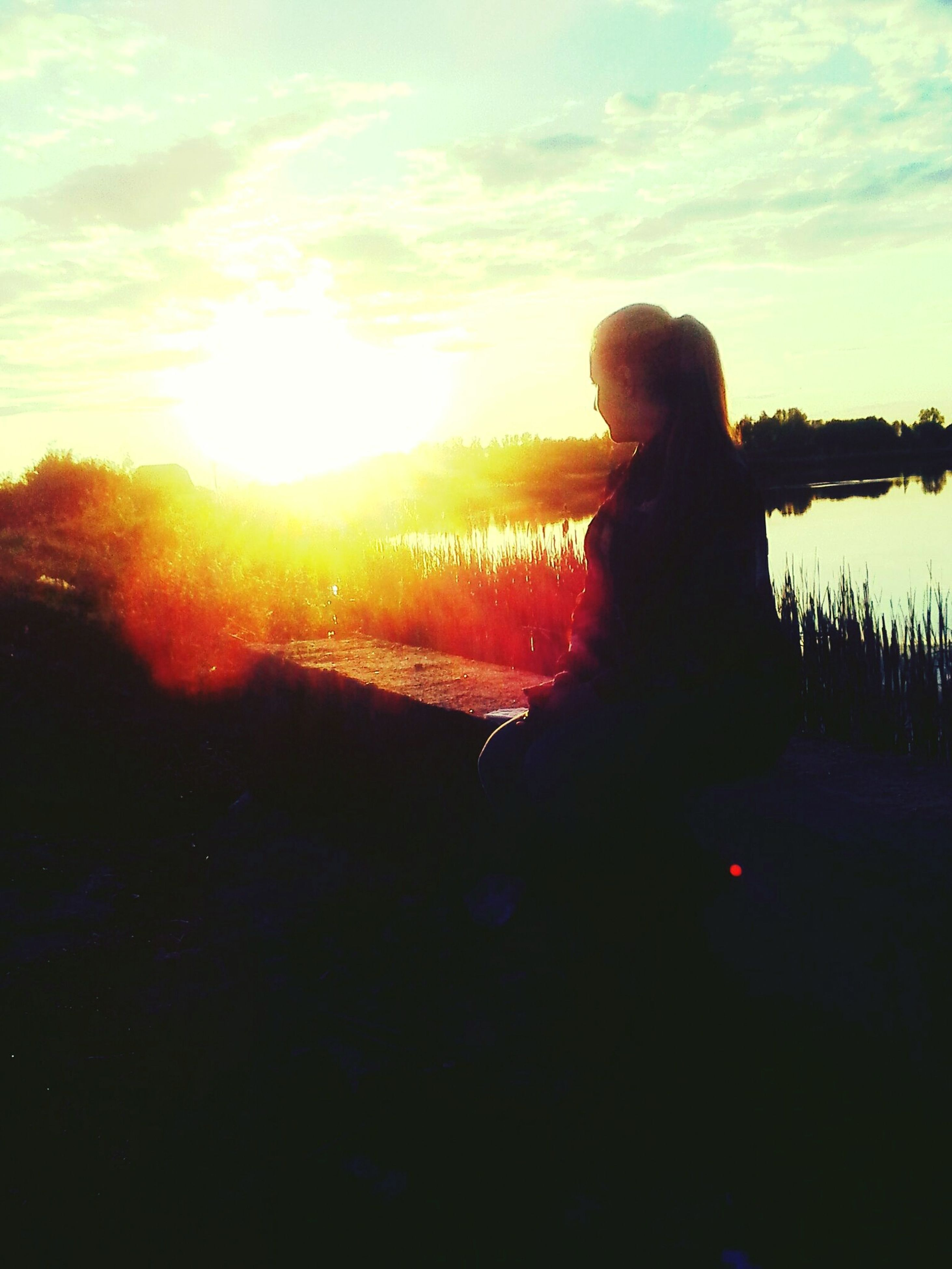 sunset, silhouette, lifestyles, leisure activity, sky, sun, water, standing, rear view, sunlight, person, three quarter length, sitting, cloud - sky, nature, waist up, tranquil scene, tranquility