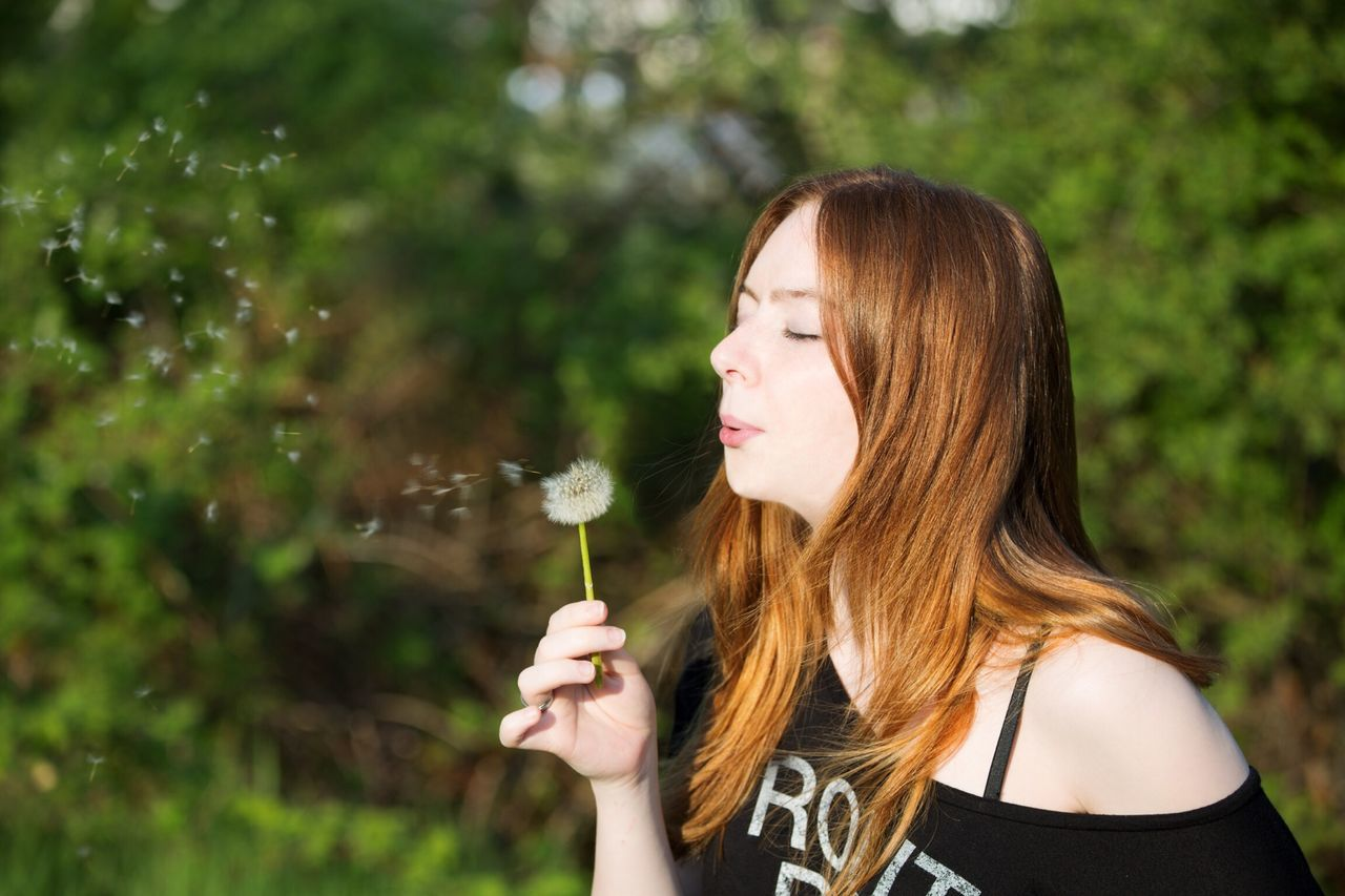 Beautiful young woman blowing dandelion at park
