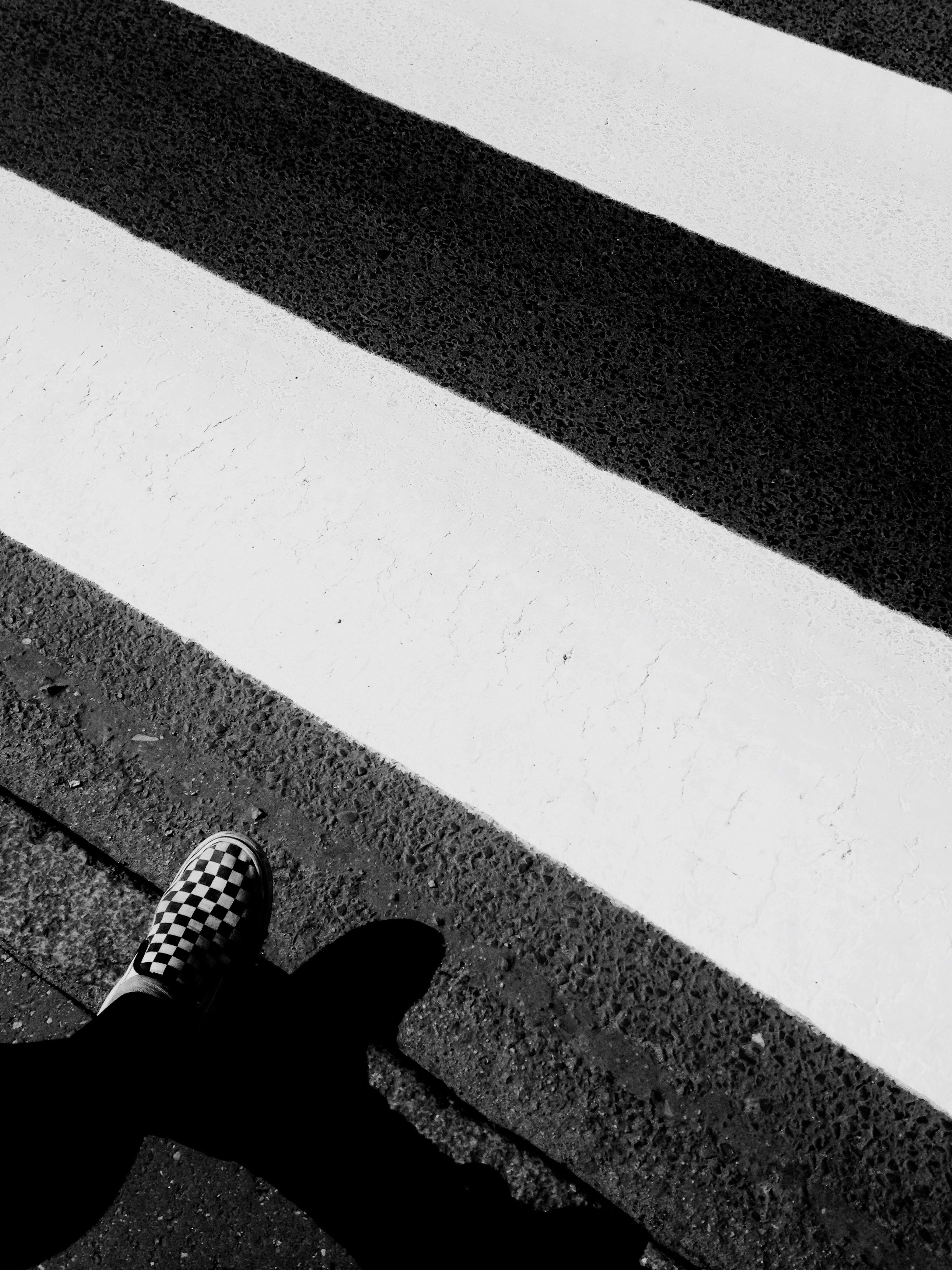 low section, person, high angle view, street, personal perspective, lifestyles, shadow, unrecognizable person, sunlight, men, road, leisure activity, part of, shoe, road marking, human foot, day