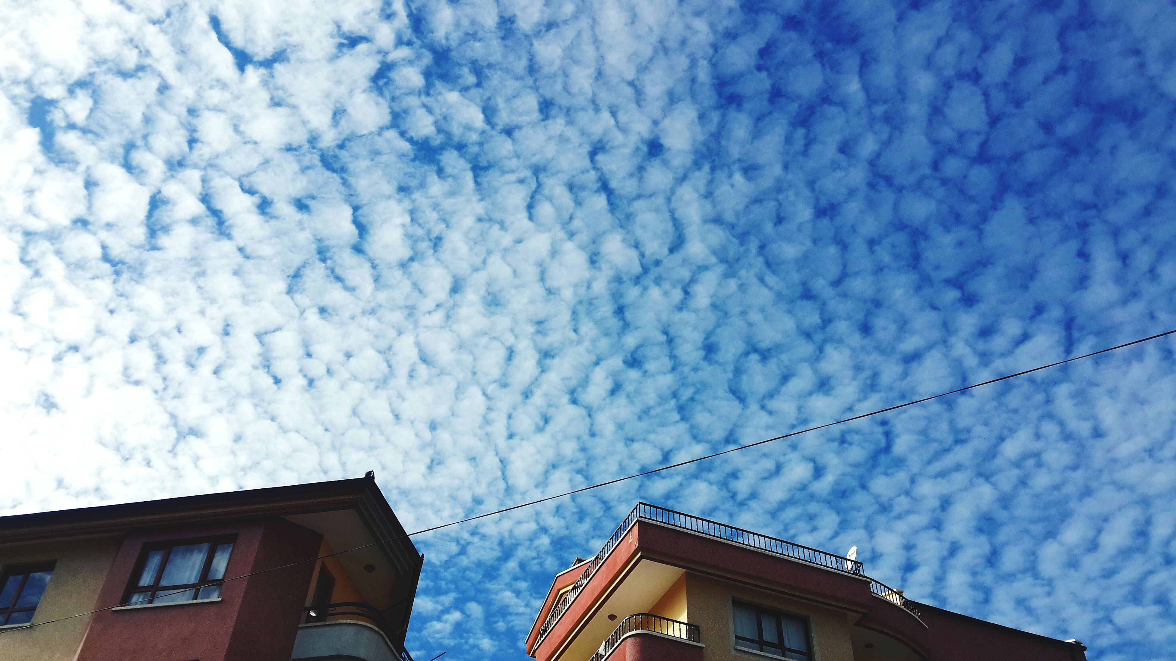low angle view, building exterior, architecture, built structure, sky, high section, cloud - sky, residential structure, house, residential building, cloudy, building, cloud, outdoors, day, blue, no people, city, power line, roof