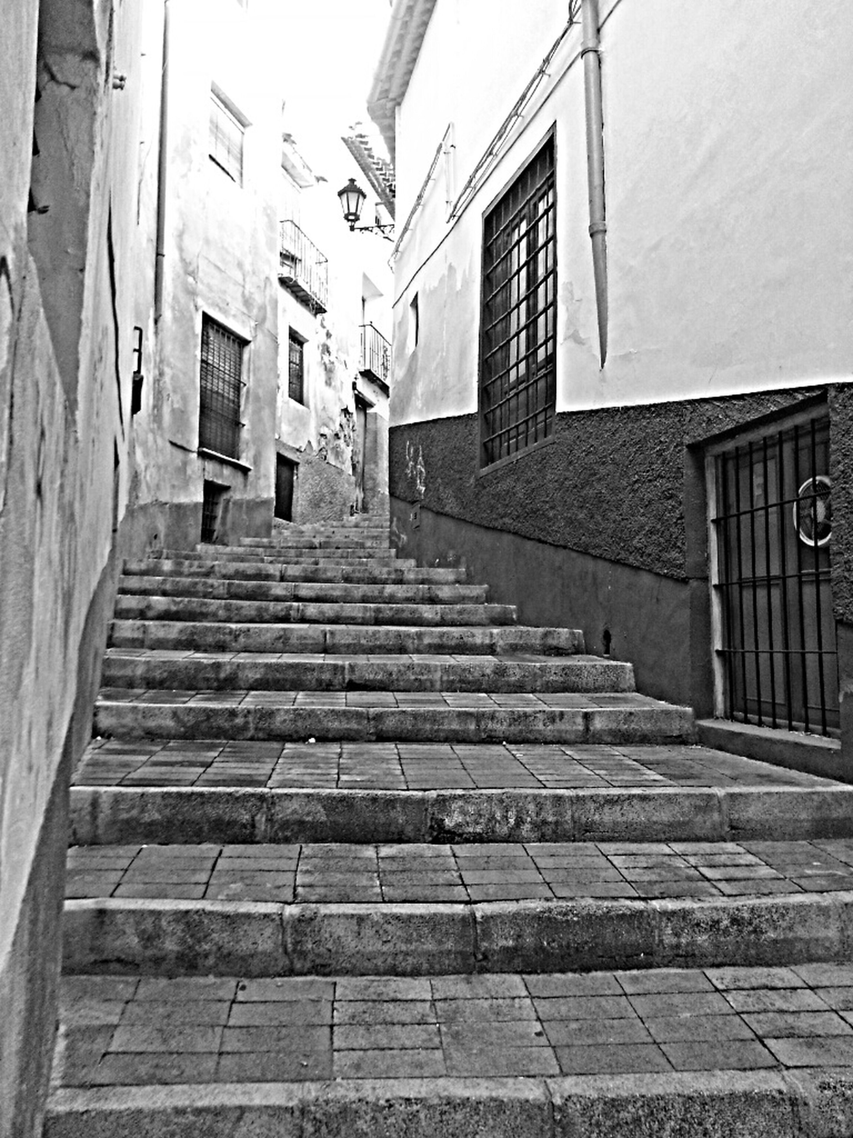 building exterior, architecture, built structure, the way forward, steps, building, residential structure, residential building, steps and staircases, house, staircase, railing, low angle view, city, street, cobblestone, diminishing perspective, day, wall - building feature, street light
