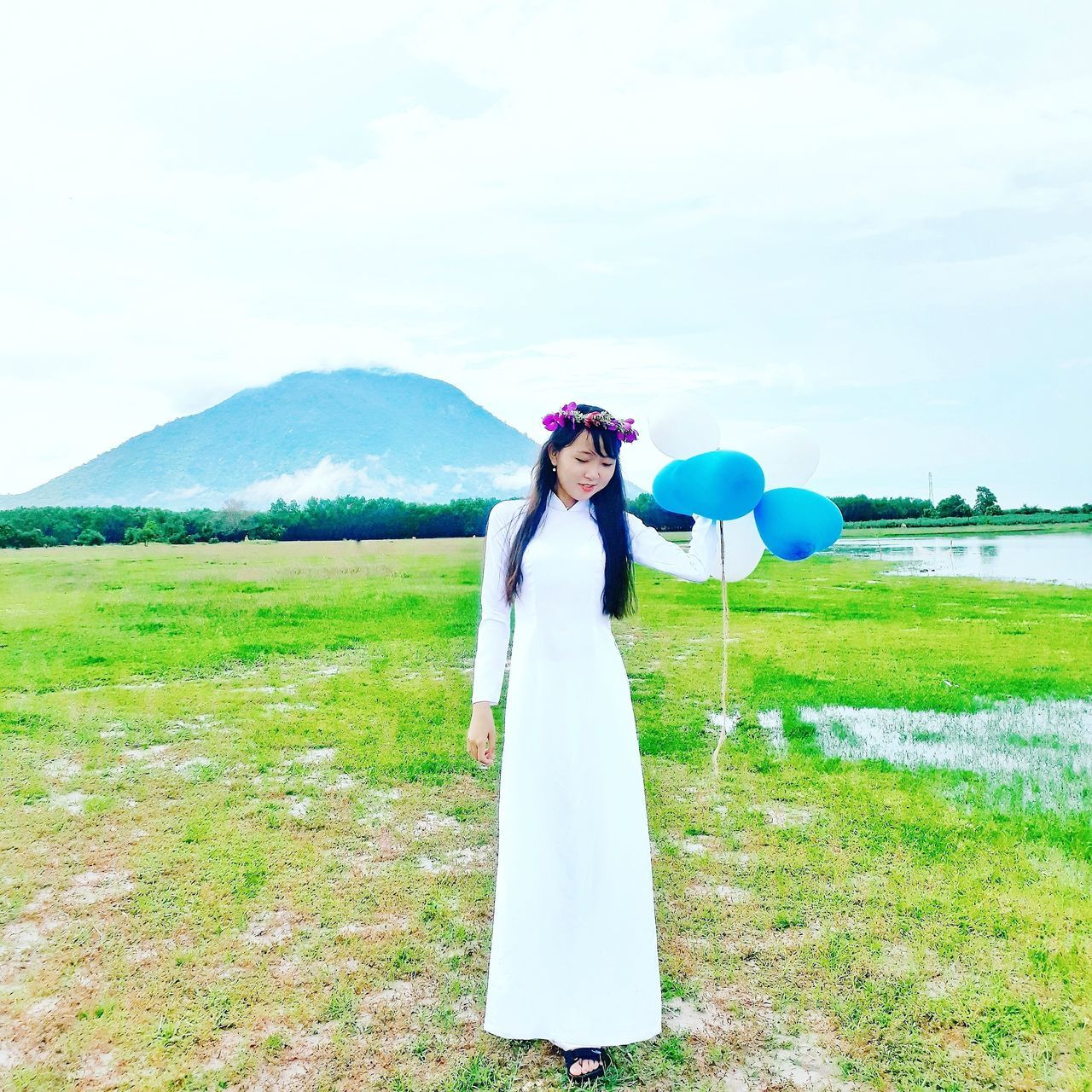 standing, real people, one person, balloon, green color, grass, nature, sky, field, young adult, cloud - sky, young women, beauty in nature, day, portrait, looking at camera, happiness, scenics, outdoors, lifestyles, smiling, growth, women, beautiful woman, full length, bride, people