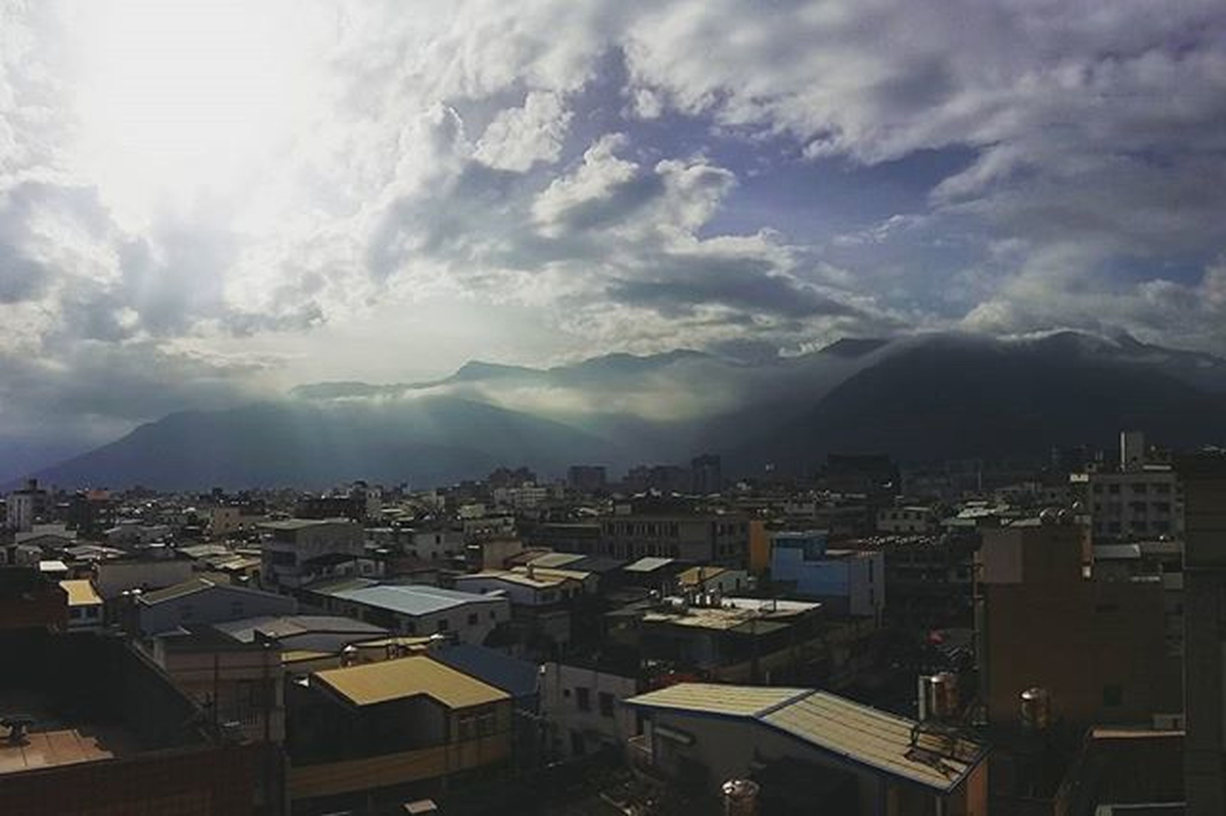 building exterior, architecture, built structure, sky, cityscape, cloud - sky, residential district, city, residential structure, residential building, mountain, high angle view, house, crowded, town, cloudy, townscape, cloud, weather, community