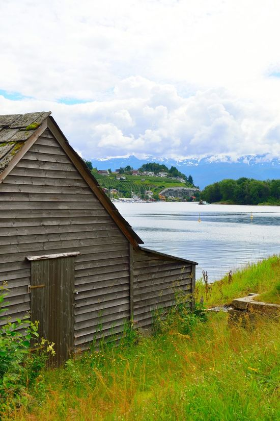 Barn by the shore in Norheimsund, Norway. Boats in the background. Barn Beauty In Nature Blue Cloud - Sky Day Fjord Grass Mountain Nature No People Norheimsund Norway Outdoors Sea Sky Thatched Roof Tree Water