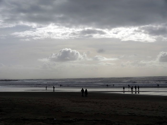 Atlantic Ocean Beach Beauty In Nature Cloud - Sky Clouds And Waves Coastline Horizon Over Water Incidental People Nature And People Rain Over The Ocean Sand Shore Silhouette Surfers