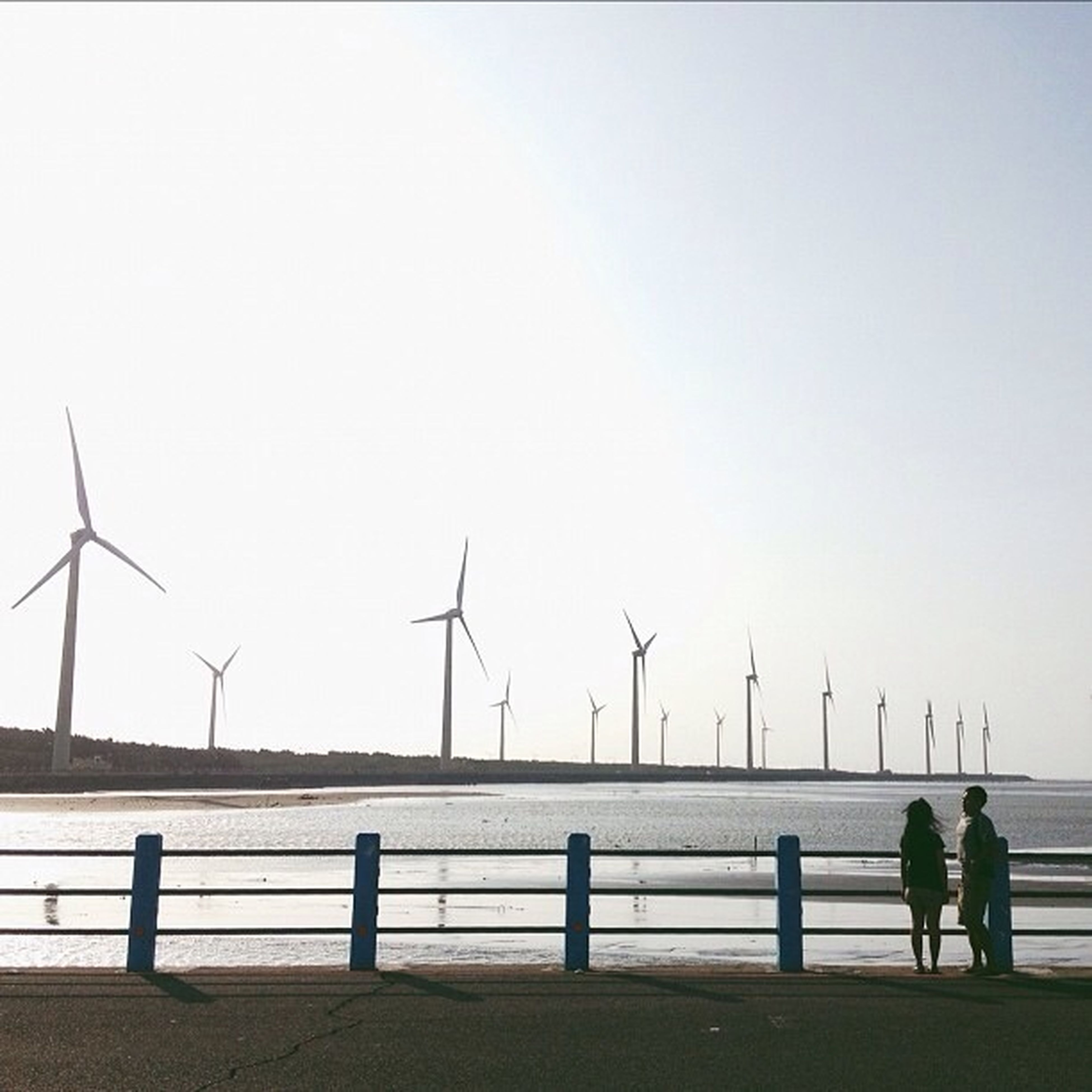 water, sea, men, copy space, clear sky, crane - construction machinery, crane, sky, silhouette, lifestyles, leisure activity, standing, railing, built structure, nature, commercial dock, person, pier