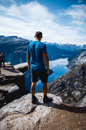 Hiker looking down at Trolltunga One Man Only Mountain Full Length Landscape Adventure Cloud - Sky Nature Trolltunga Trolltunganorway Backpacking Travelphotography Travel Destinations Mountain Peak Snowcapped Mountain Norway Is Peaceful Norway Norway Nature Scenics Looking At View Beauty In Nature Mountain Range Backpacker