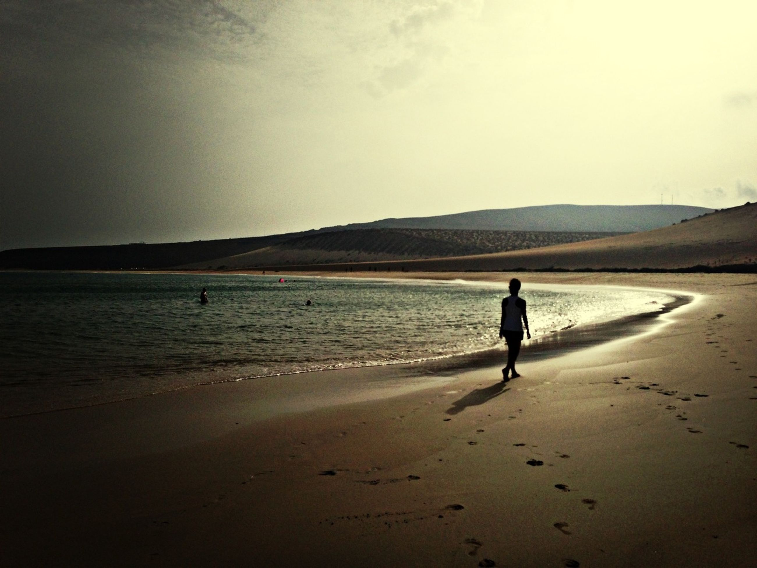 sand, beach, full length, leisure activity, lifestyles, silhouette, men, walking, shore, tranquil scene, mountain, tranquility, scenics, water, sea, rear view, nature, beauty in nature