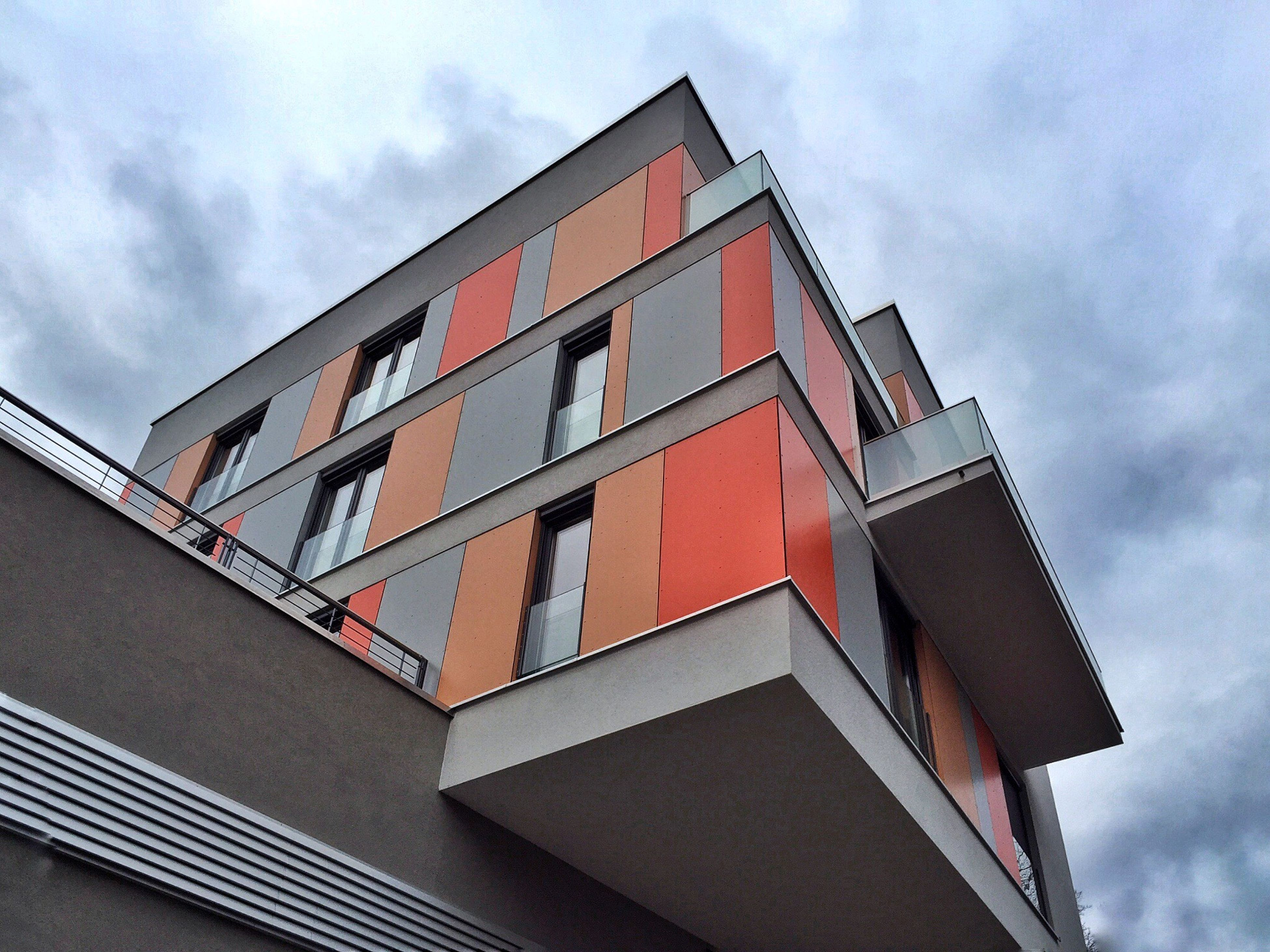 architecture, building exterior, built structure, low angle view, sky, window, cloud - sky, residential structure, building, residential building, cloud, house, cloudy, day, city, outdoors, no people, high section, balcony, glass - material