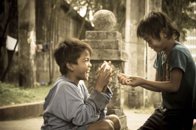 Two Boy Sharing Food along the street of manila Philippines. Day EyeemPhilippines Happiness Intramuros Manila Outdoors Person Philippines Priceless Street Child Streetphotography Togetherness