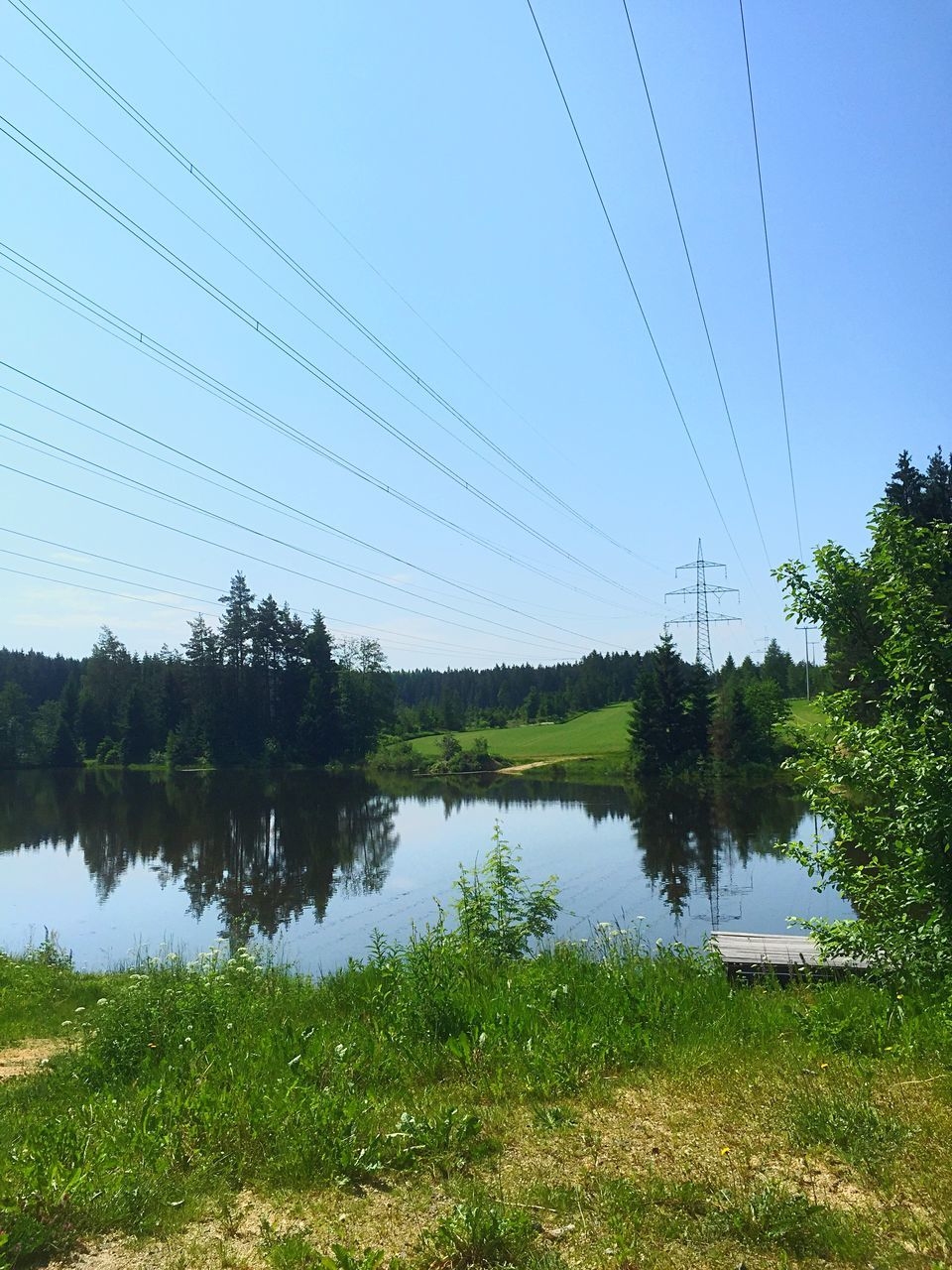 Tranquil View Of Lake Against Power Cables And Clear Sky