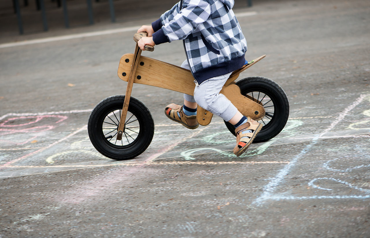 Asphalt Adult Bicycle Child Childhood Day Full Length Hopscotch Human Body Part Human Hand Leisure Activity Lifestyles Low Section Men Motion One Boy Only One Person Outdoors People Real People Riding Stunt Transportation Wooden Bicycle Wooden Bike
