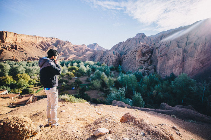 Adventure Africa Arabic Casual Clothing Day Exploration Full Length Hiking Landscape Leisure Activity Morocco Mountain Nature One Person Outdoors Photographing Real People Rear View Rock - Object Rock Formation Scenics Standing Tranquil Scene Travel Travel Destinations