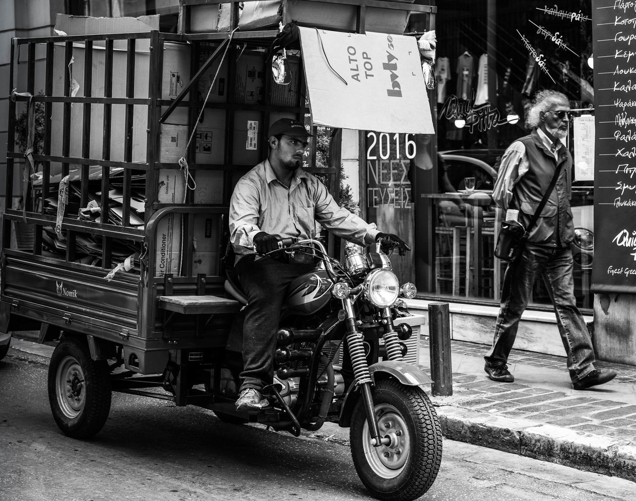 transportation, real people, land vehicle, men, mode of transport, motorcycle, full length, street, lifestyles, riding, outdoors, day, built structure, architecture, road, building exterior, one person, sitting, city, biker, adult, adults only, people
