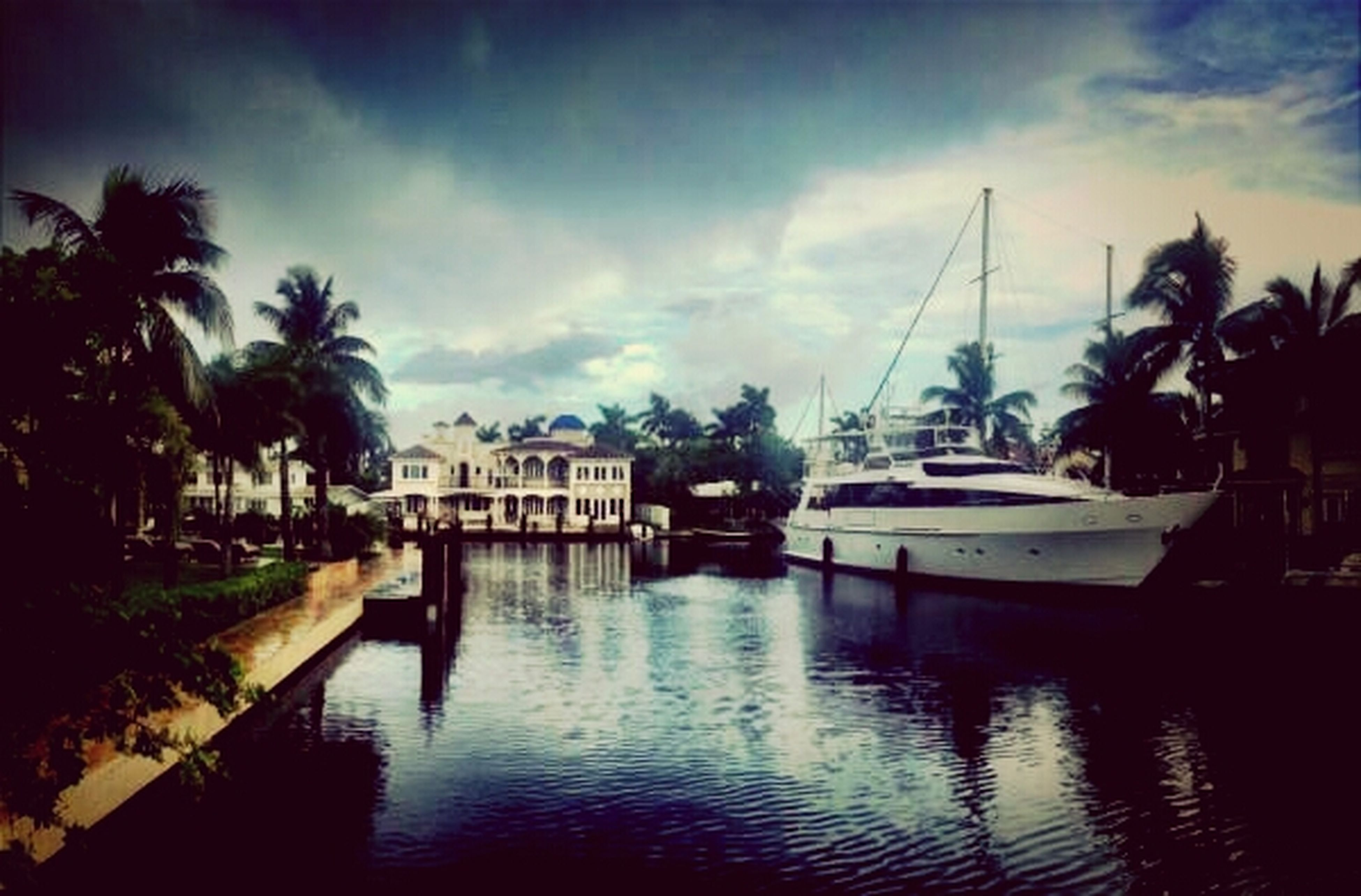 water, sky, waterfront, tree, nautical vessel, cloud - sky, transportation, moored, built structure, reflection, boat, architecture, mode of transport, river, building exterior, palm tree, cloud, cloudy, outdoors, sunset