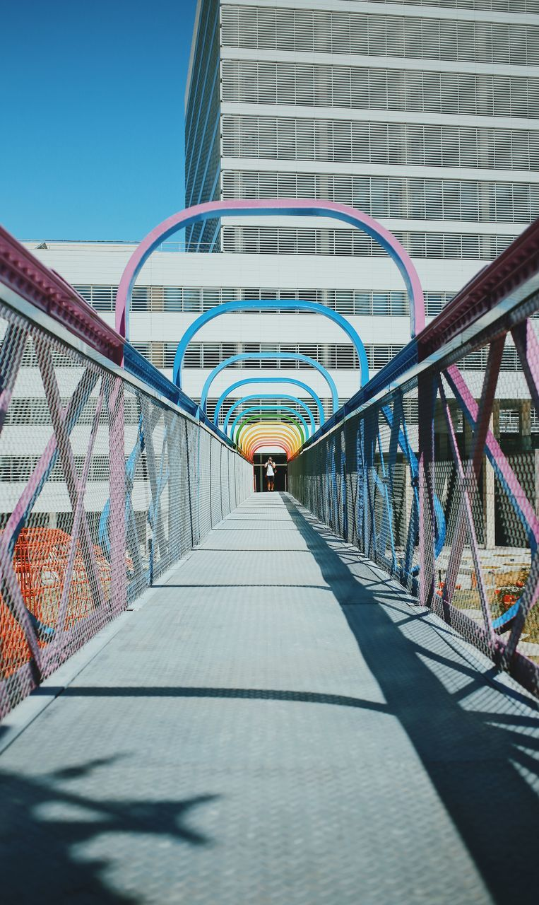 architecture, the way forward, built structure, connection, railing, real people, day, building exterior, modern, rear view, bridge - man made structure, footbridge, one person, outdoors, covered bridge, men, full length, clear sky, city, people