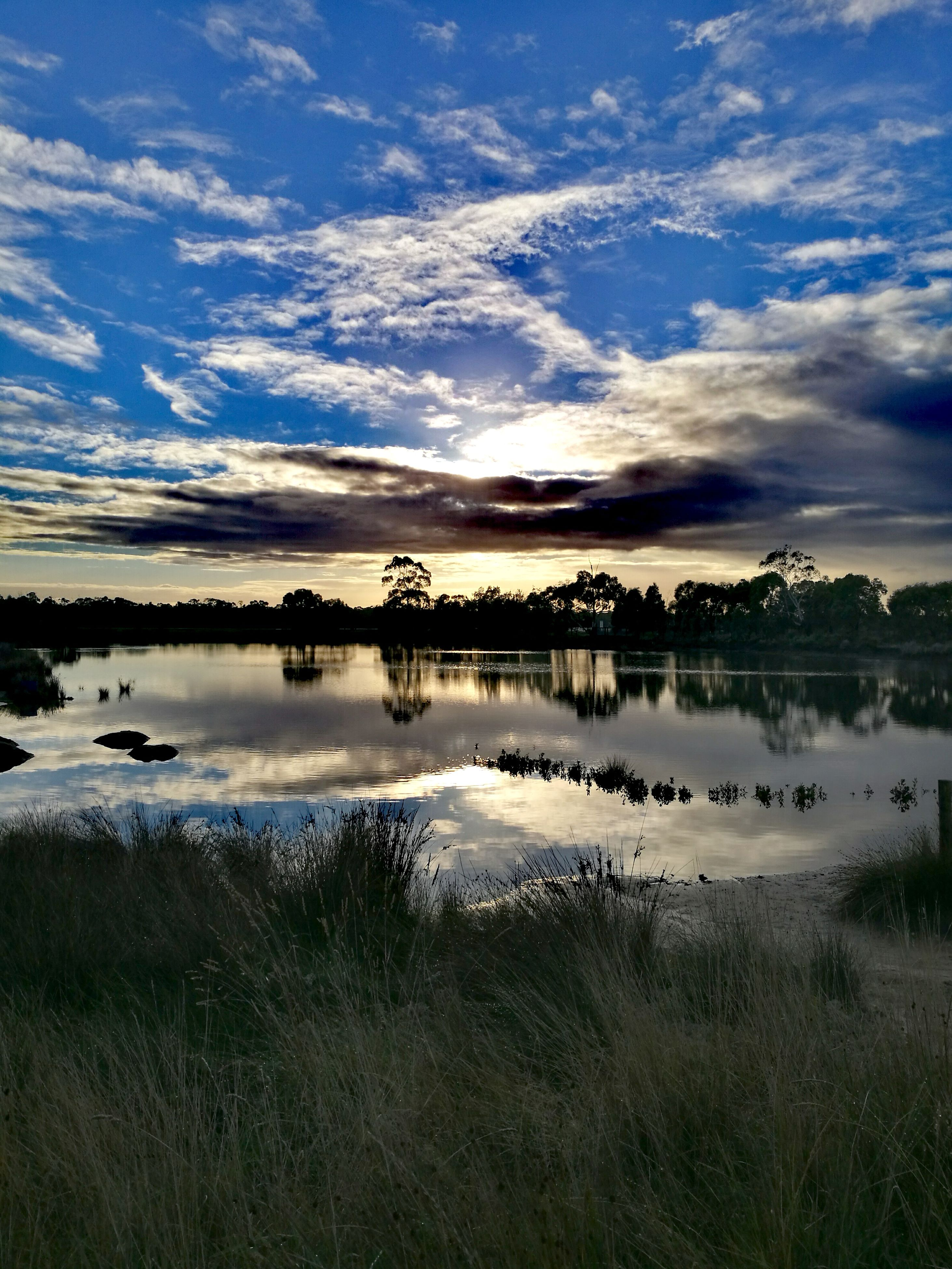 reflection, water, tranquil scene, sky, nature, tranquility, lake, outdoors, cloud - sky, grass, beauty in nature, no people, scenics, landscape, sunset, day, tree