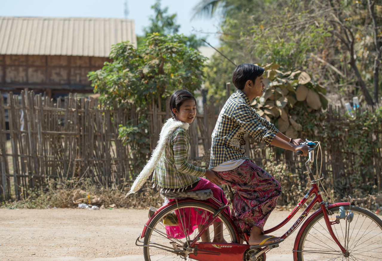 two people, real people, girls, togetherness, childhood, lifestyles, elementary age, sibling, bicycle, leisure activity, day, outdoors, boys, tree, casual clothing, transportation, happiness, building exterior, bonding, young adult, full length, sitting, young women, smiling, architecture, people