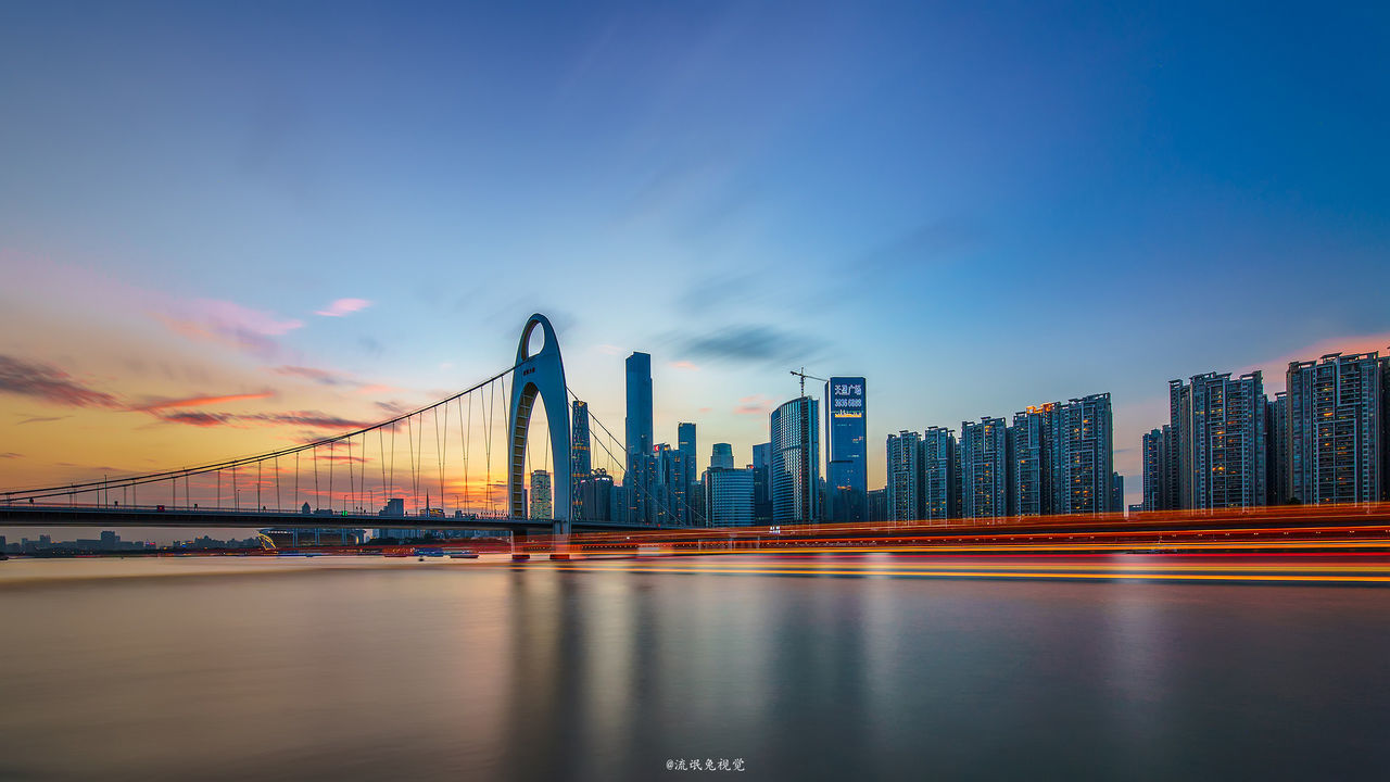 architecture, built structure, bridge - man made structure, suspension bridge, skyscraper, city, connection, building exterior, sky, travel destinations, transportation, cityscape, urban skyline, outdoors, river, water, modern, waterfront, cloud - sky, downtown district, no people, sunset, illuminated, night, nature