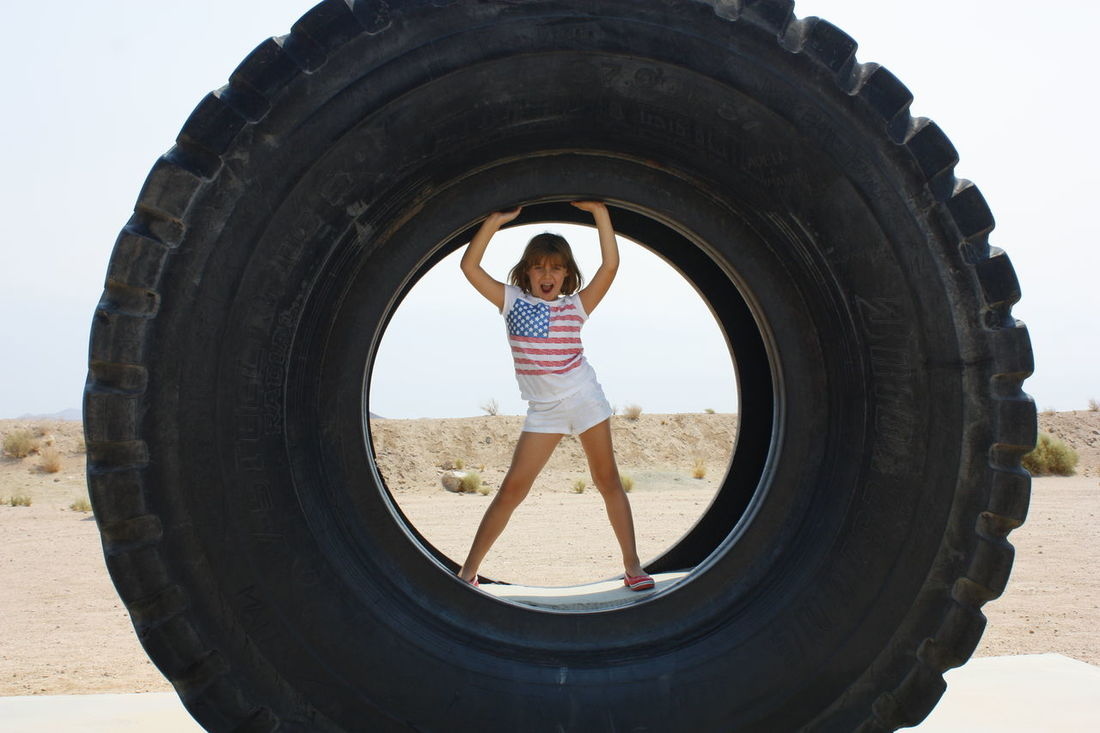 Child standing inside a giant tire Children Only Desert Full Length Leisure Activity One Person Portrait Standing Tire Tractor Tire